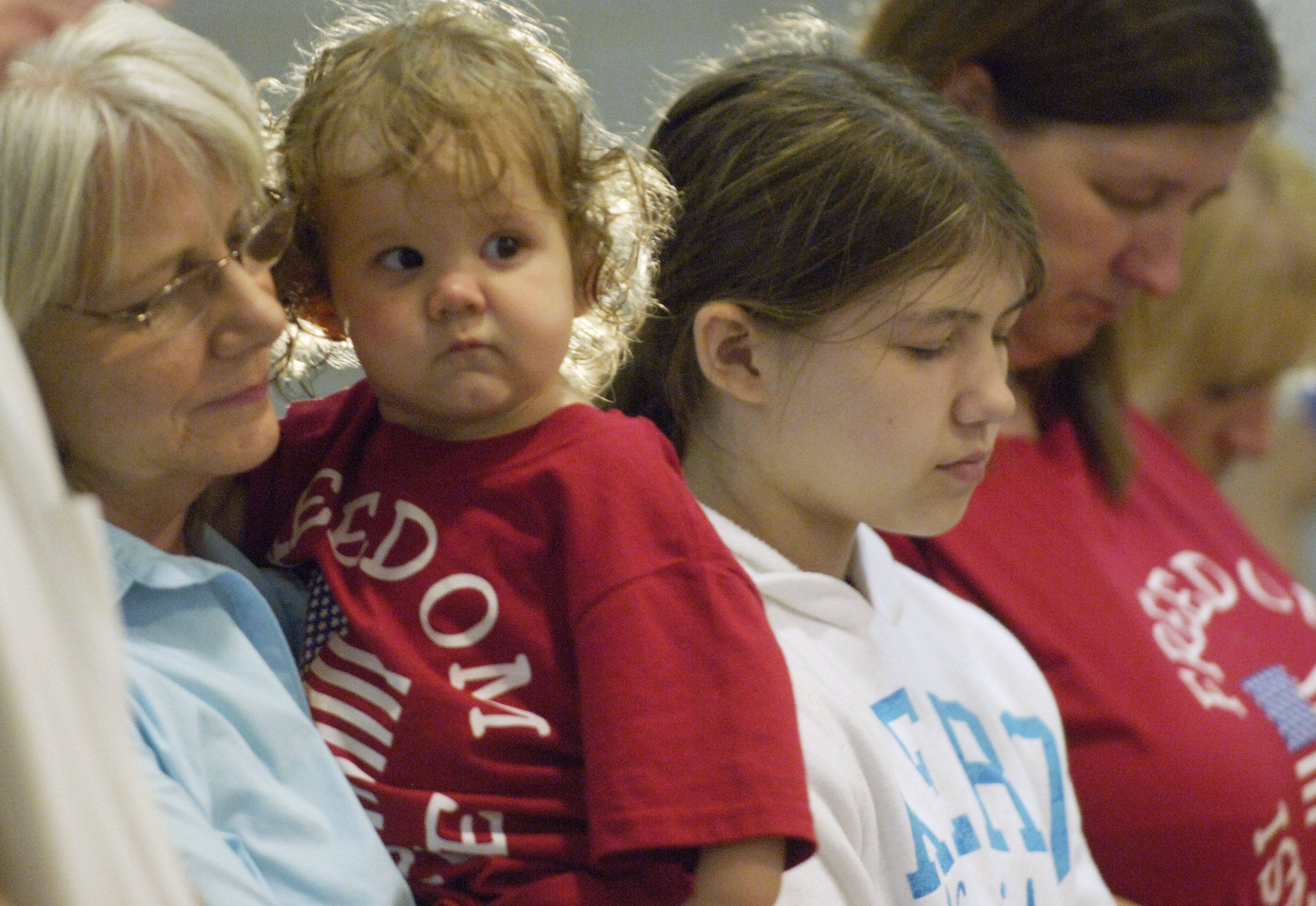 Mikayla Stack, age 18 months, is held by her grandmother, Linda Stack, at the dedication of a gym at Christian Liberty Academy in honor of Mikayla's father, James Stack. To their right are Joanne Savage and her mother, Dawn Hedrick, Mikayla's maternal grandmother.