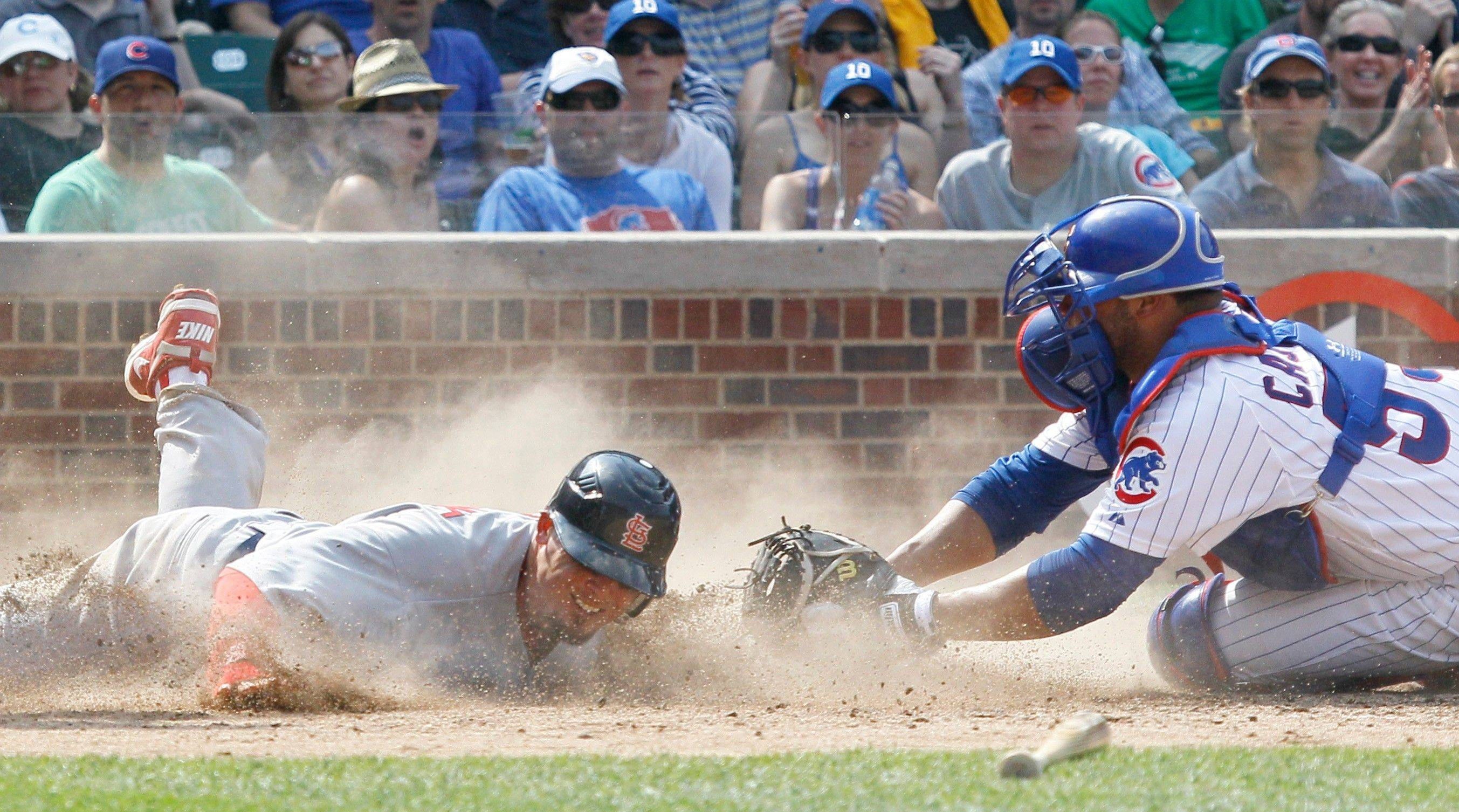 Tyler Greene, left, slides safely behind Welington Castillo to score on an RBI single by Jon Jay during the seventh inning of the Cardinals' victory over the Cubs on Thursday at Wrigley Field.