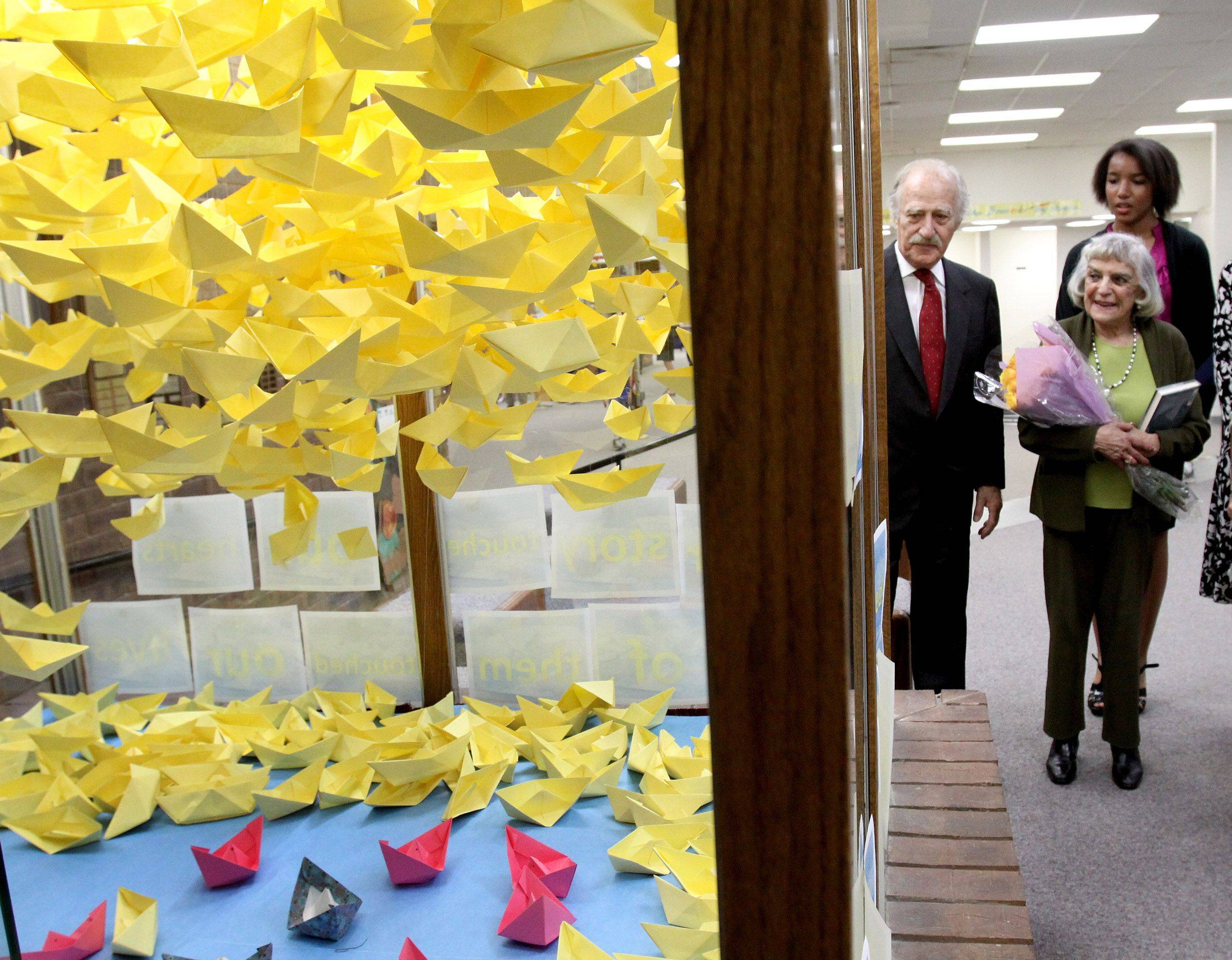 Edith Westerfeld and her husband Larry Breitkopf of Skokie, along with eighth-grader Casey Smith, take a look at a display case of origami boats, which represent the children who escaped Nazi Germany.