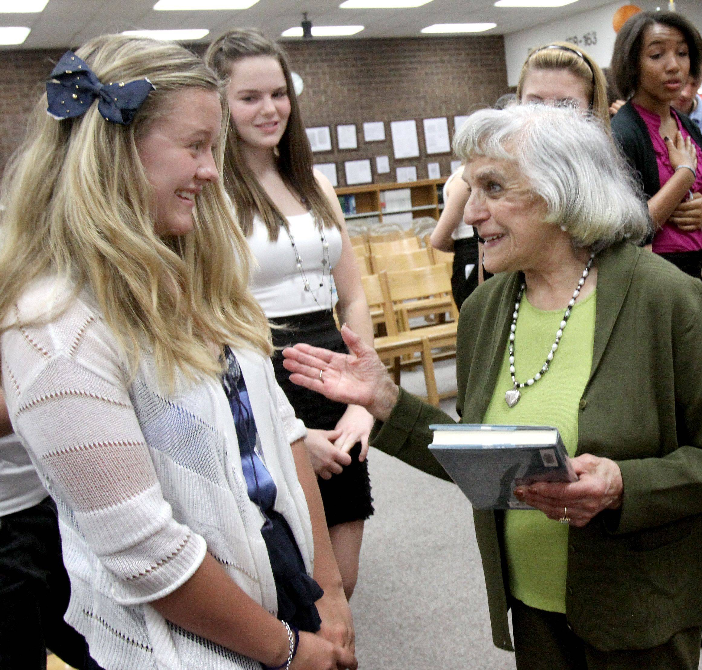 Edith Westerfeld speaks with Madison Junior High School eighth-graders Annika Lee and Amy Miller during a Friday reception held in Westerfeld's honor.