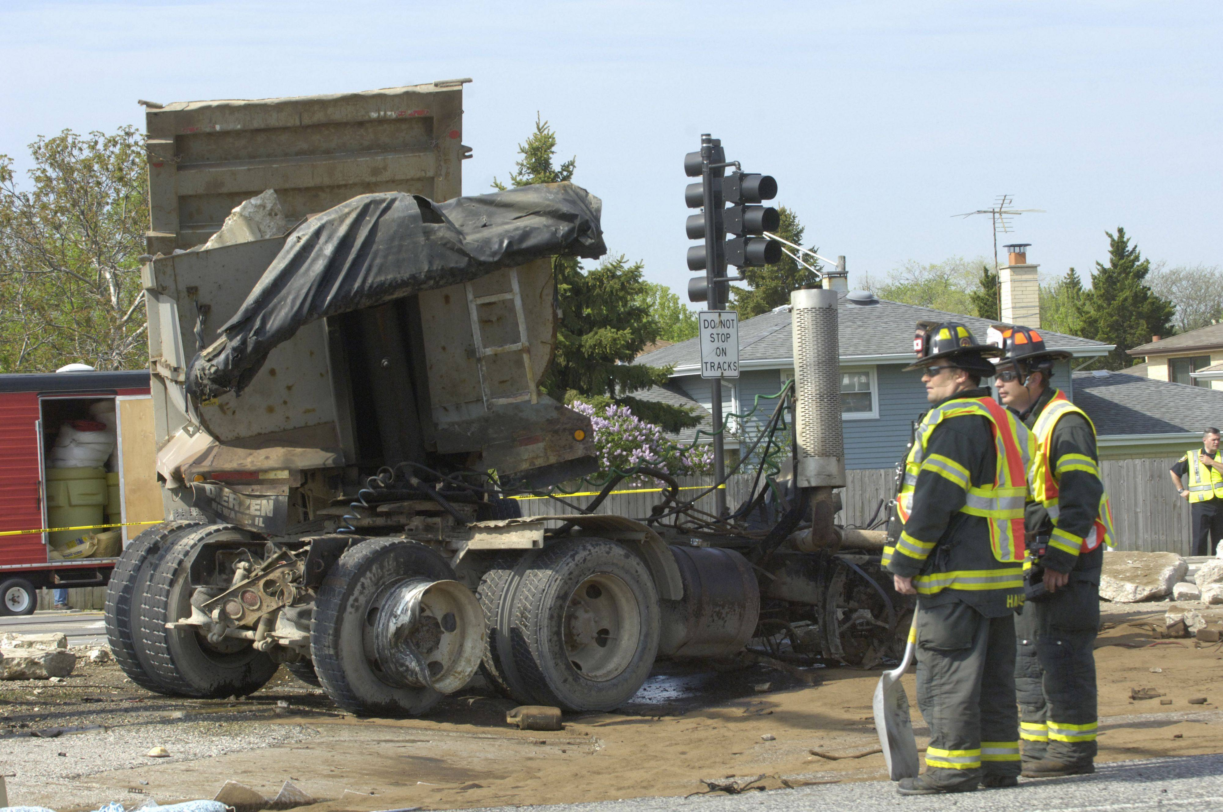 Firefighters stand near the wreckage of the truck after a Metra passenger train derailed when it struck a loaded dump truck at Mount Prospect Road Friday morning.