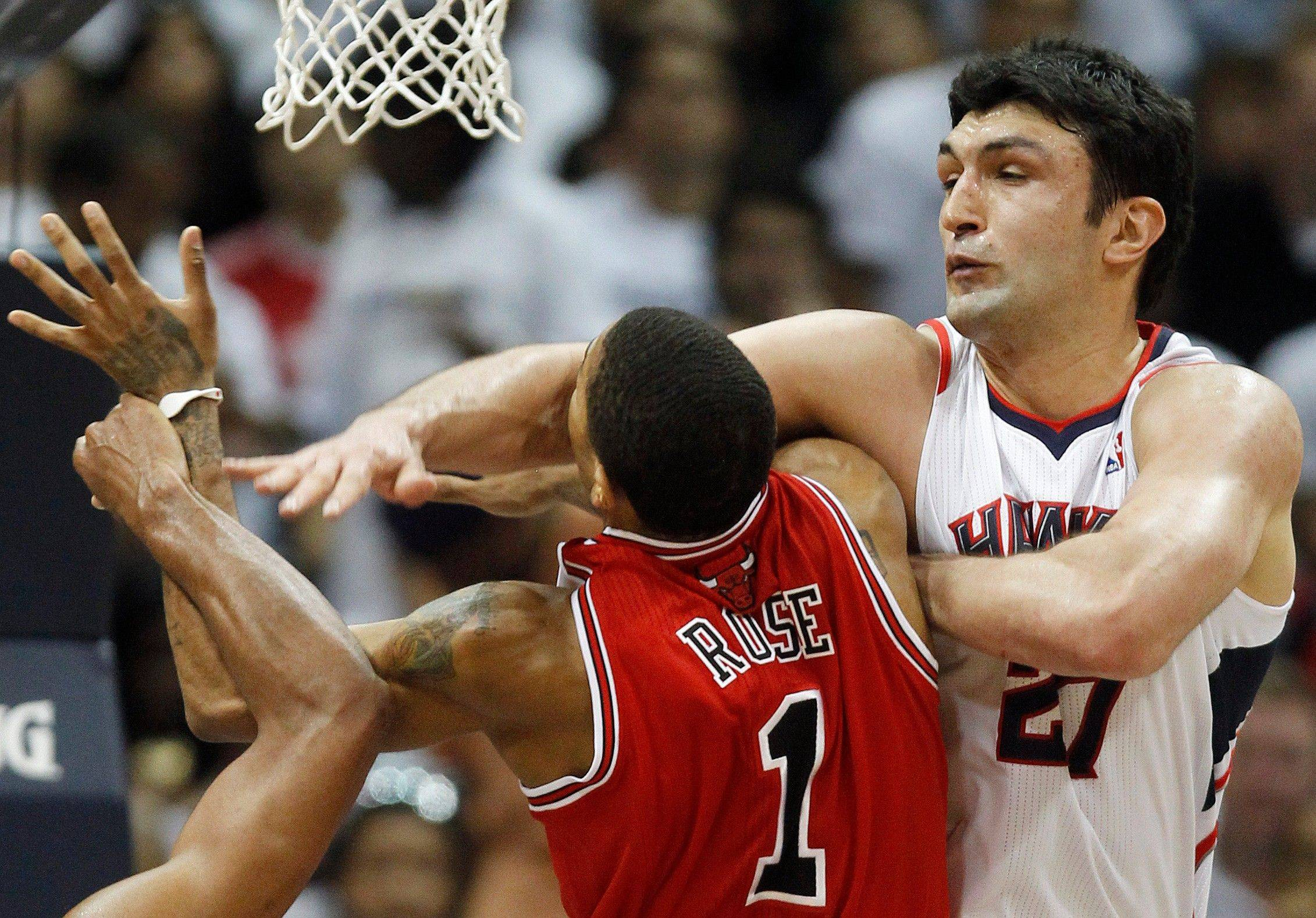 Bulls guard Derrick Rose goes to the hoop and runs into the defense of Hawks center Zaza Pachulia in Game 6 in Atlanta Thursday.