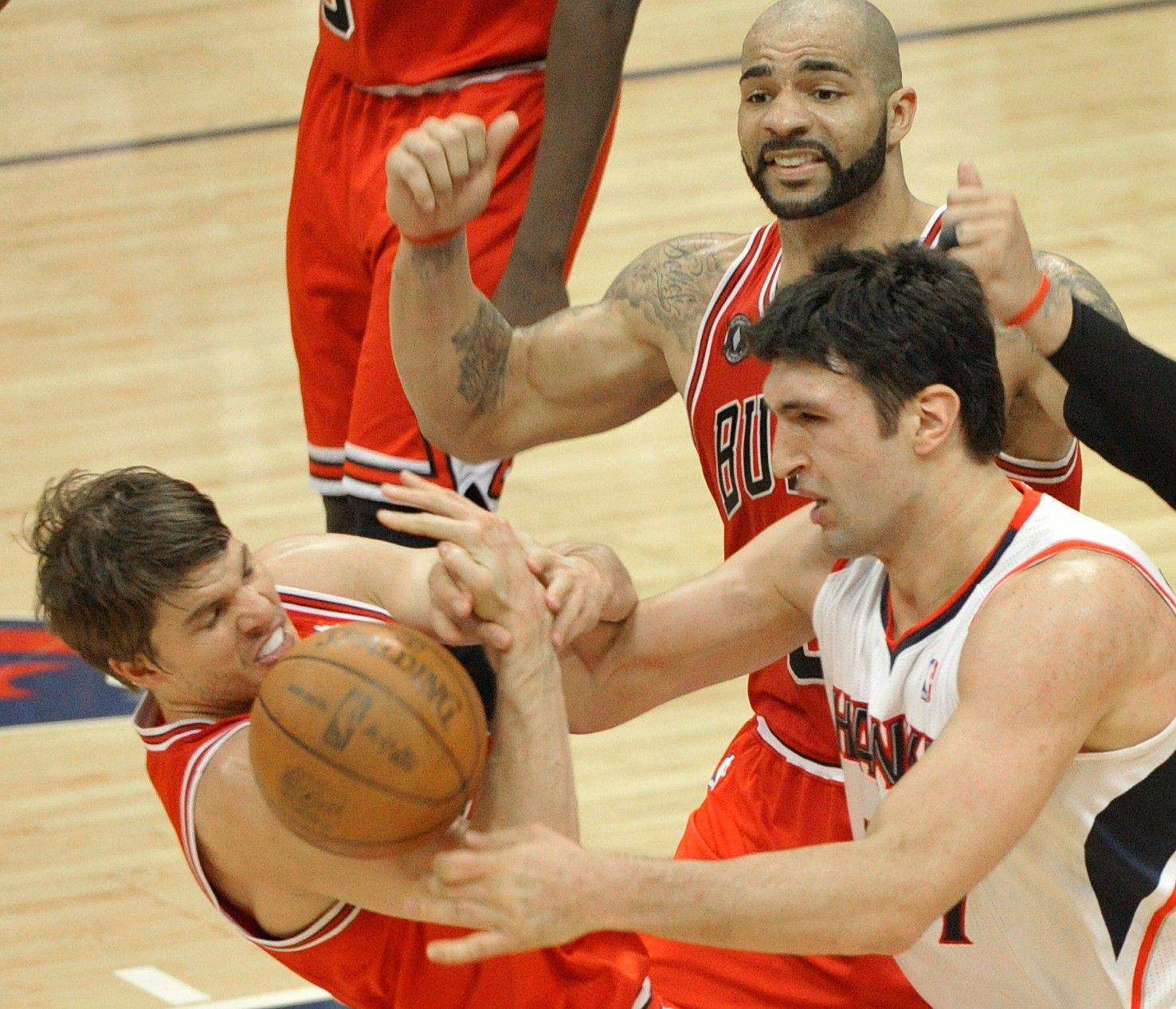 Chicago Bulls guard Kyle Korver, left, vies for a loose ball with Atlanta Hawks center Zaza Pachulia as Bulls forward Carlos Boozer looks on in the second quarter Thursday.