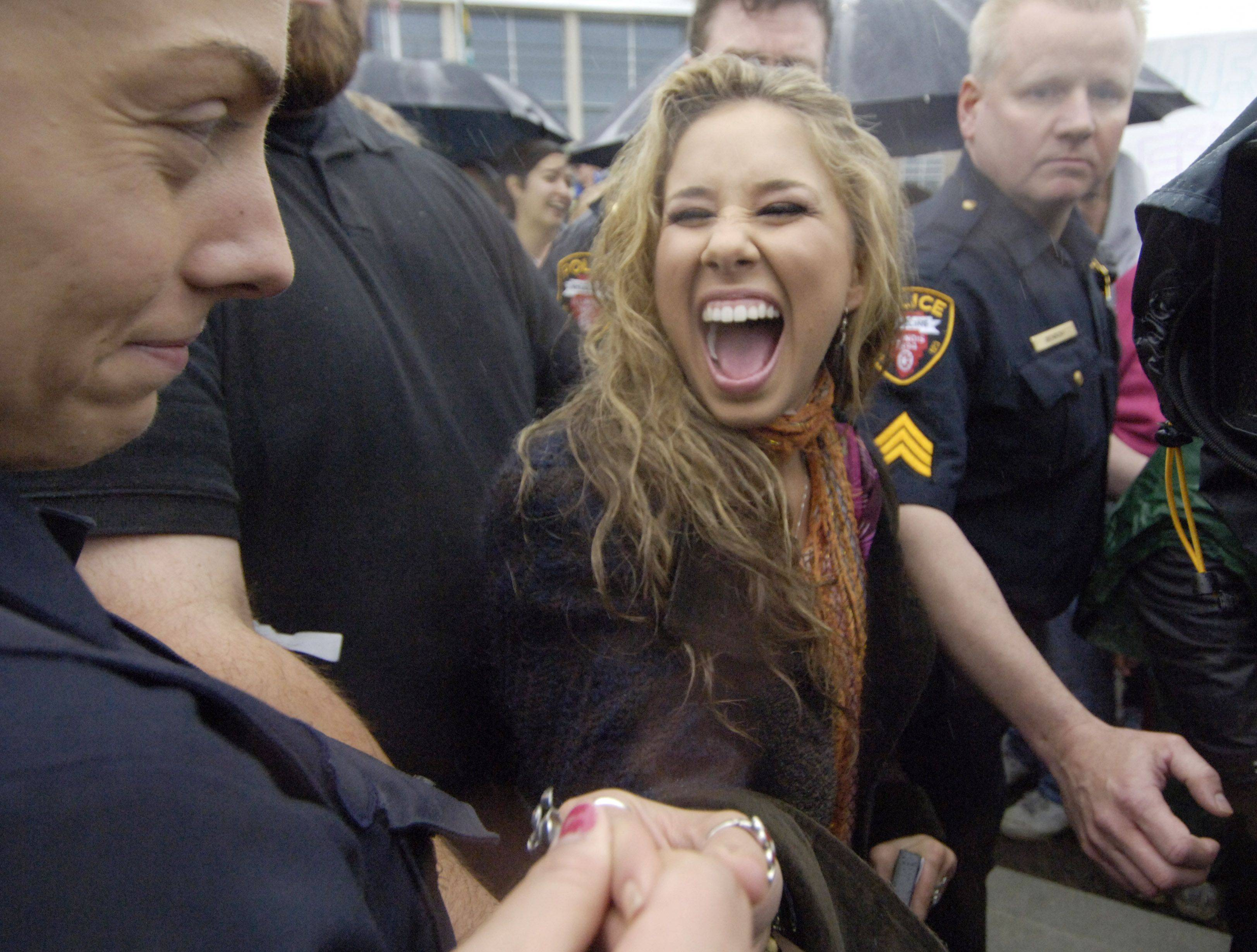 American Idol finalist Haley Reinhart is escorted back to her limo after a gathering at the Wheeling Village Hall Saturday