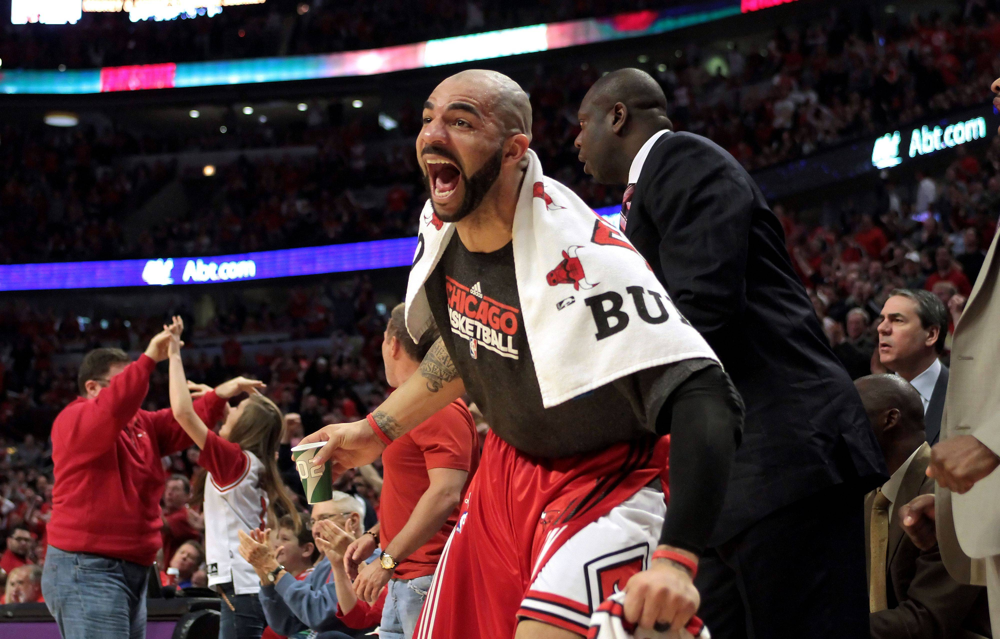 Chicago Bulls power forward Carlos Boozer cheers after a dunk by Taj Gibson during game one of the Eastern Conference finals Sunday night at the United Center.