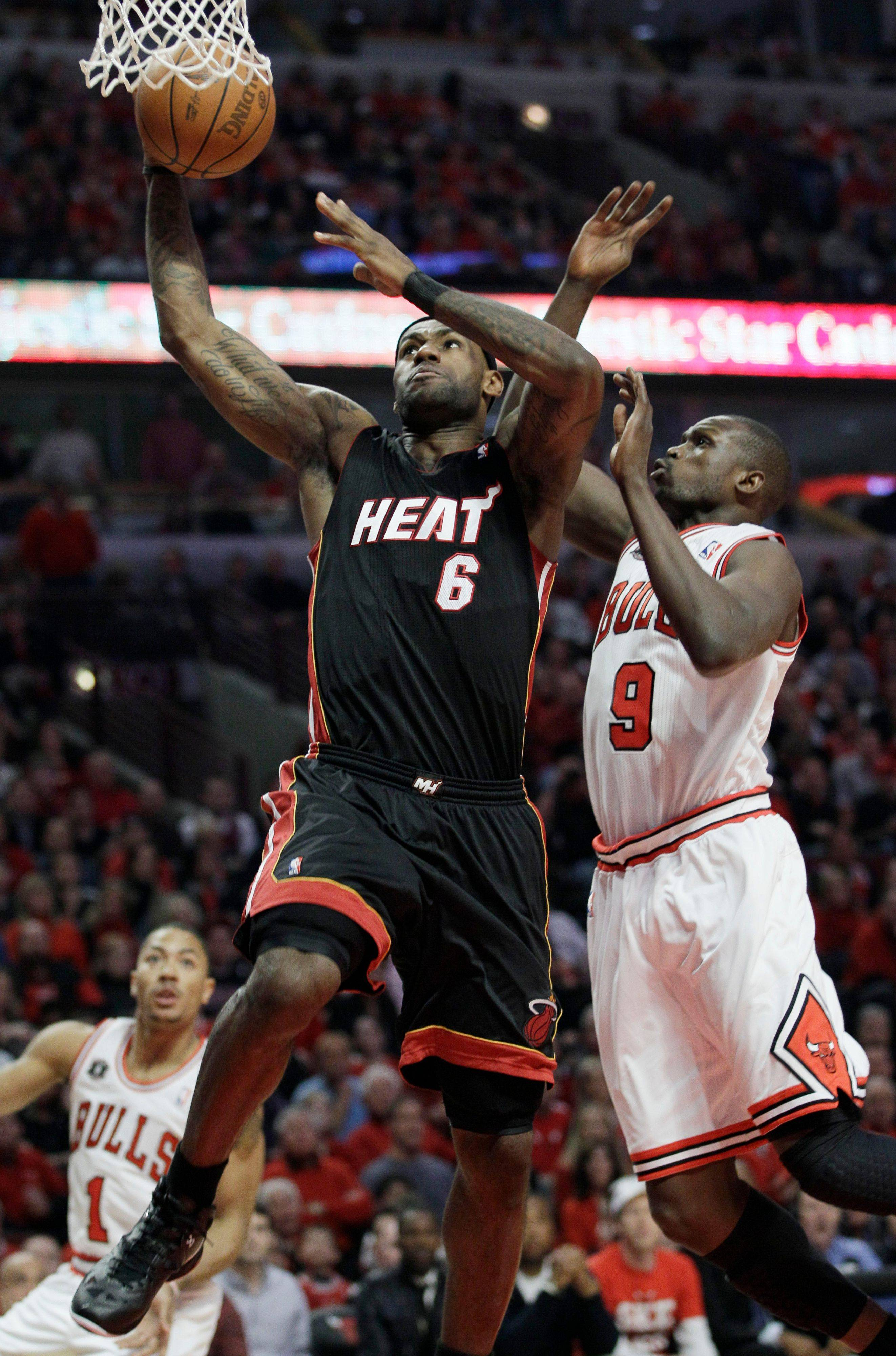 Miami Heat's LeBron James, left, drives to the basket past Chicago Bulls' Luol Deng during the first quarter.