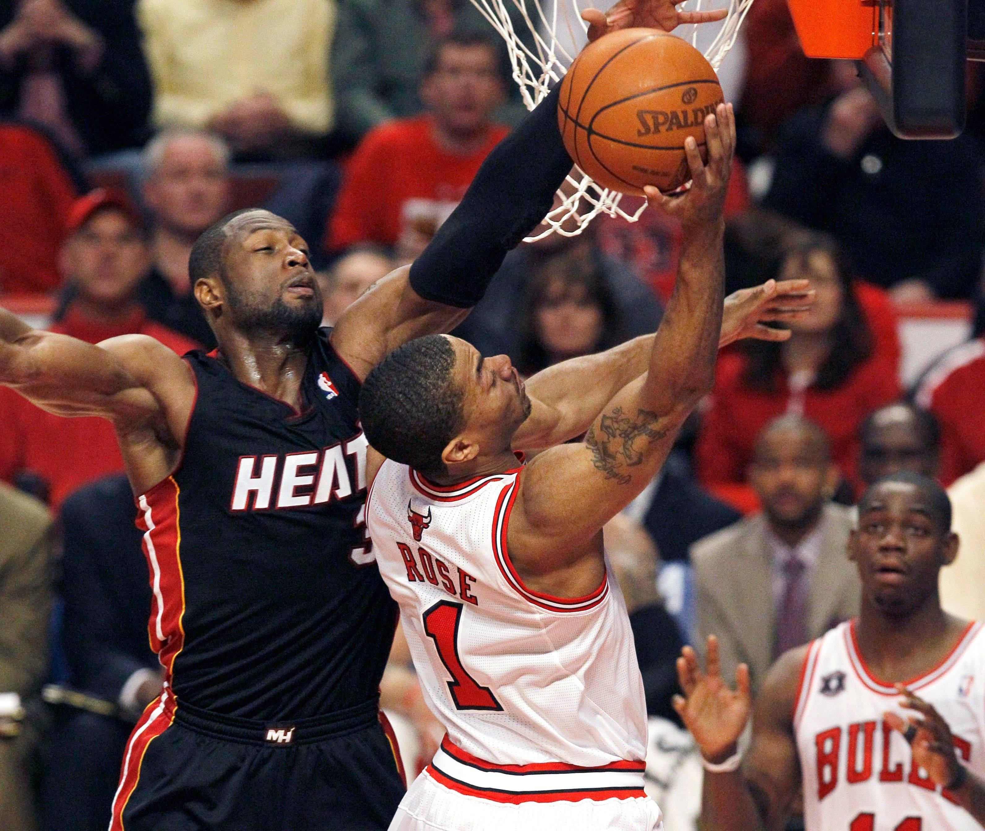 Chicago Bulls guard Derrick Rose, right, shoots over the out stretched arm of Miami Heat guard Dwyane Wade during the first quarter.