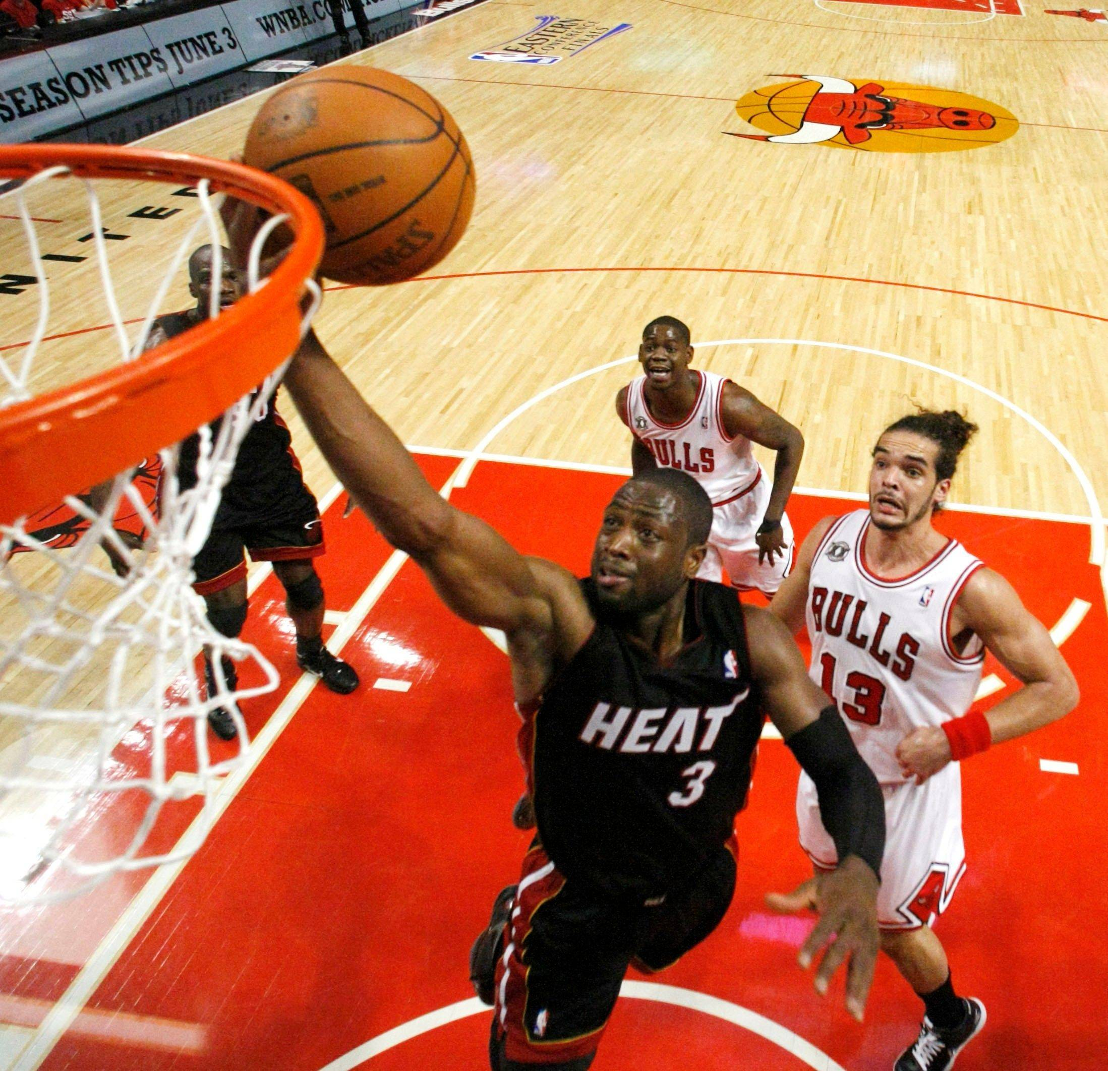 Miami Heat shooting guard Dwyane Wade, left, shoots past the defense of Chicago Bulls center Joakim Noah, right, and Ronnie Brewer during the second quarter.