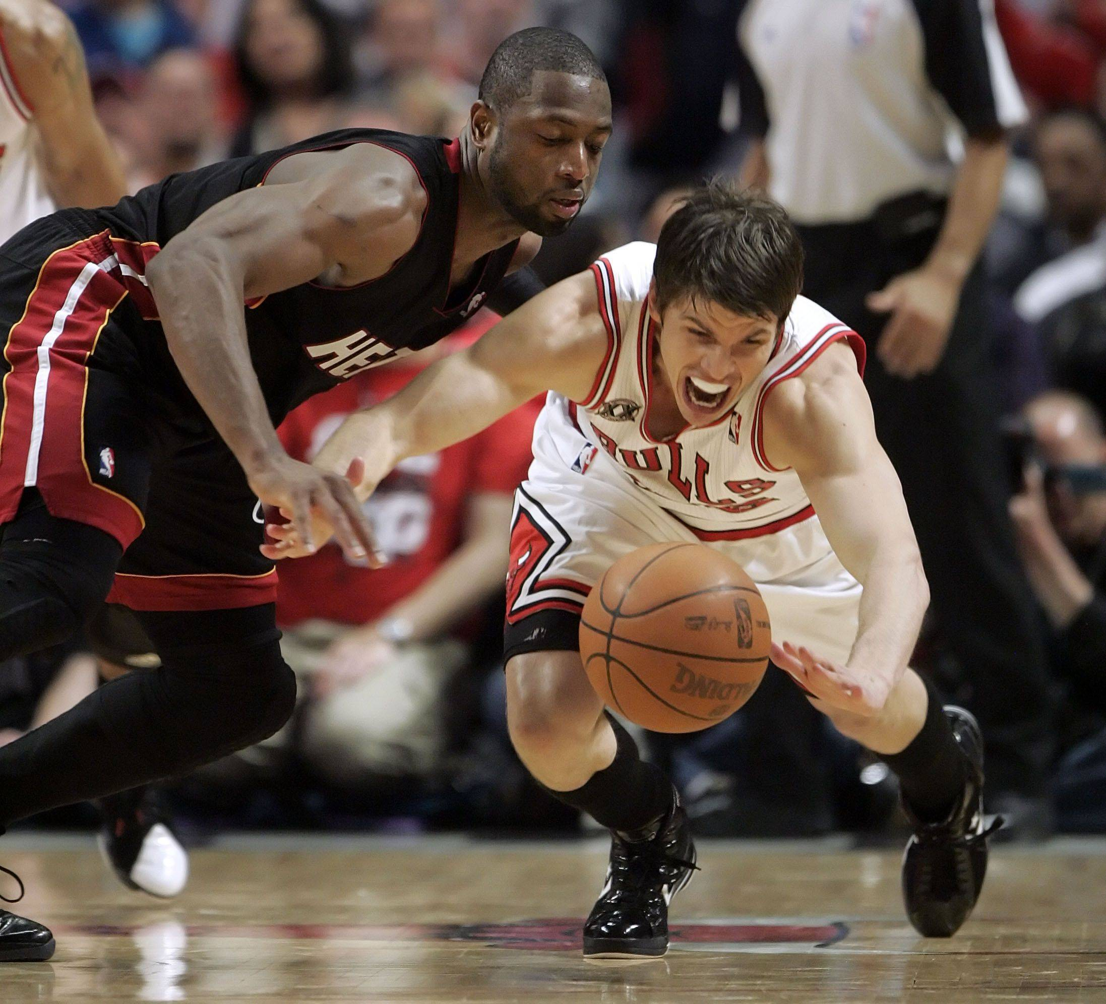 Chicago Bulls shooting guard Kyle Korver and Miami Heat shooting guard Dwyane Wade battle for a loose ball during game one of the Eastern Conference finals Sunday night at the United Center.