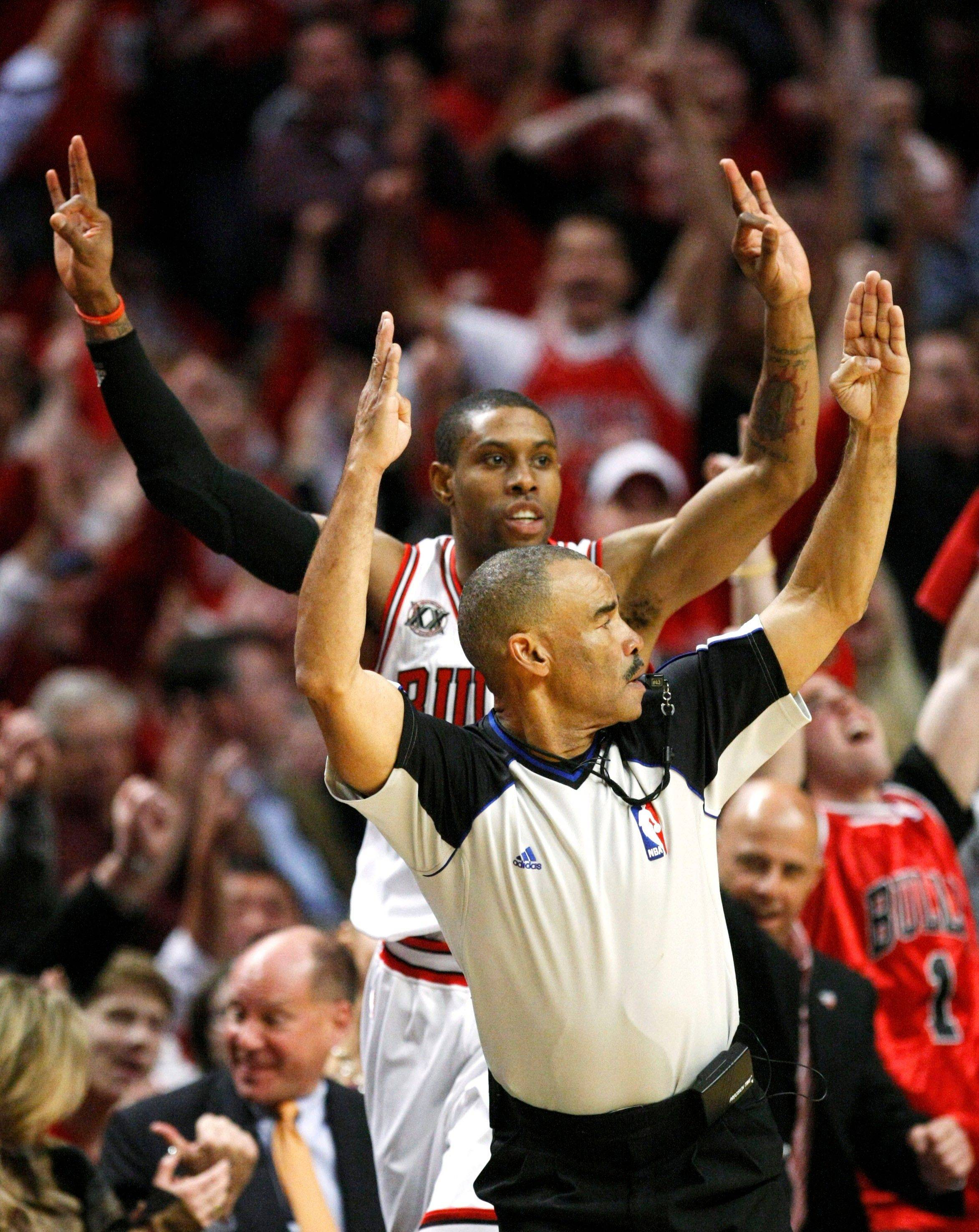 NBA referee Dan Crawford, foreground, and Chicago Bulls point guard C.J. Watson signal his three-point shot during the fourth quarter. The Bulls defeated the Heat 103-82 Sunday.