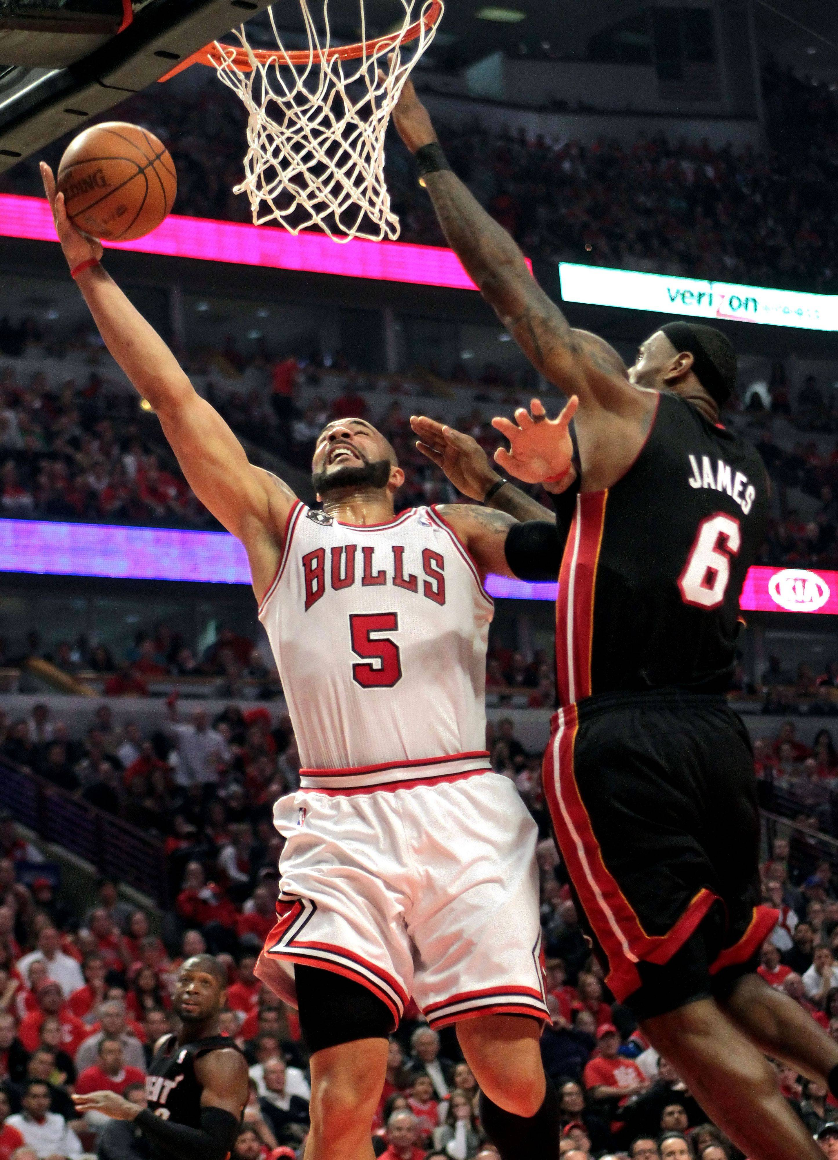 Chicago Bulls power forward Carlos Boozer drives on Miami Heat small forward LeBron James during the first quarter.
