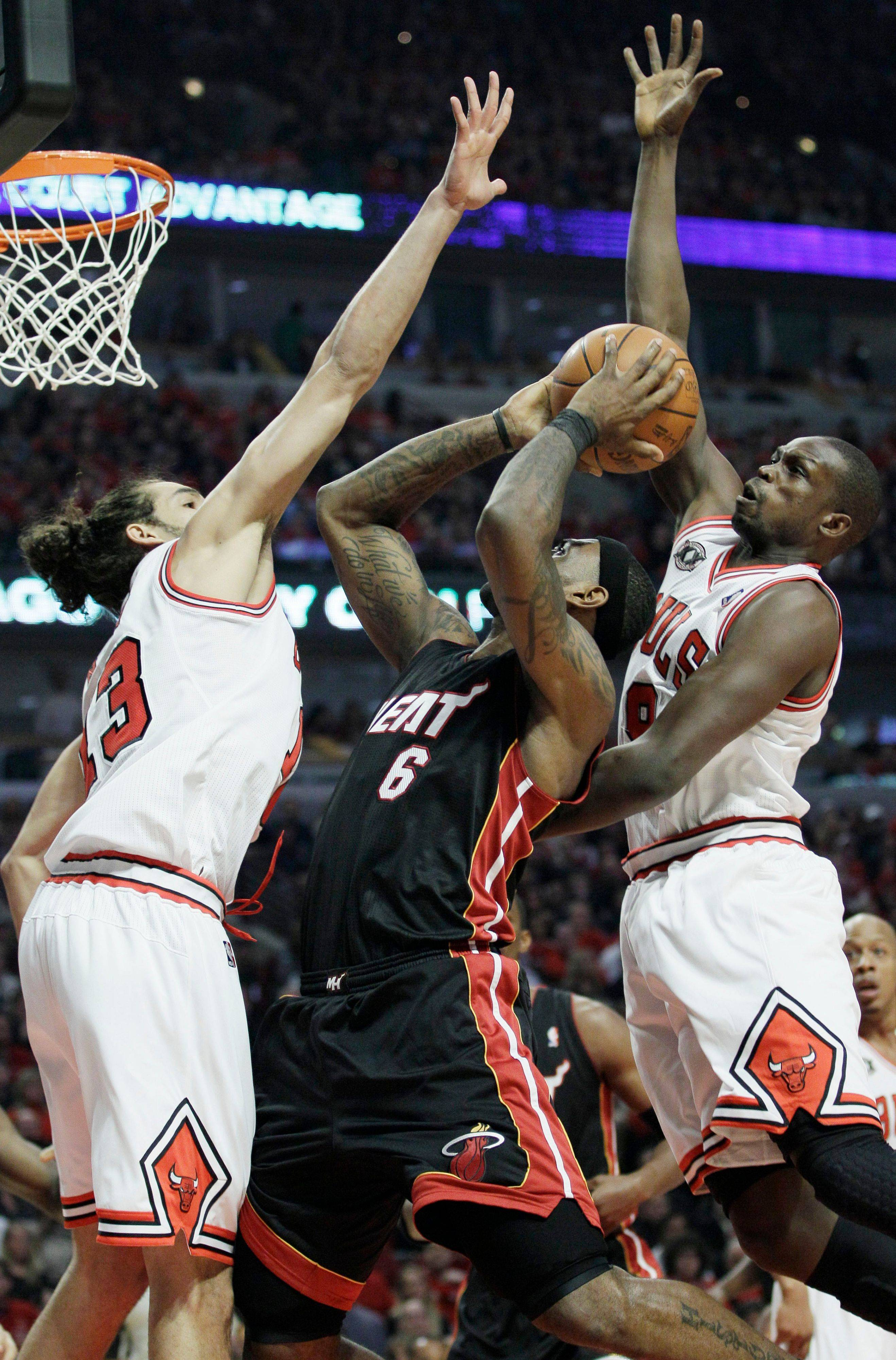 Miami Heat's LeBron James, center, goes up for a shot against Chicago Bulls' Joakim Noah, left, and Luol Deng during the first quarter.