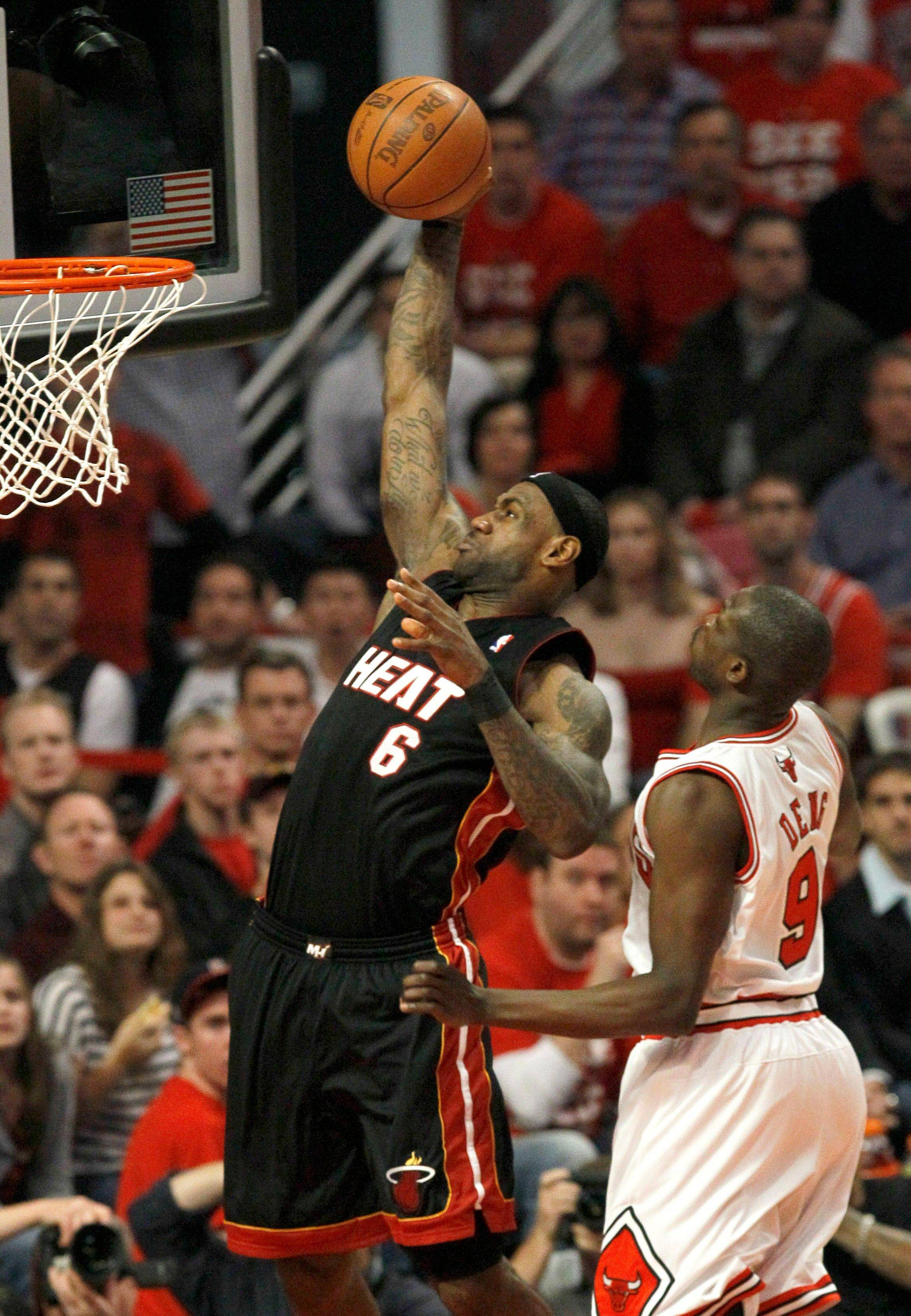 Miami Heat forward LeBron James, left, dunks past Chicago Bulls forward Luol Deng during the first quarter.