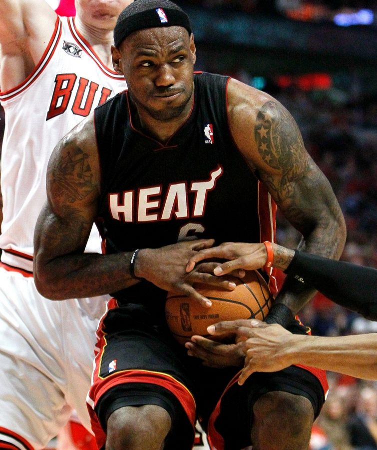 Miami Heat forward LeBron James struggles holding onto the ball with Bulls point guard C.J. Watson during the fourth quarter in Game 1 of the NBA Eastern Conference Finals basketball series Sunday.
