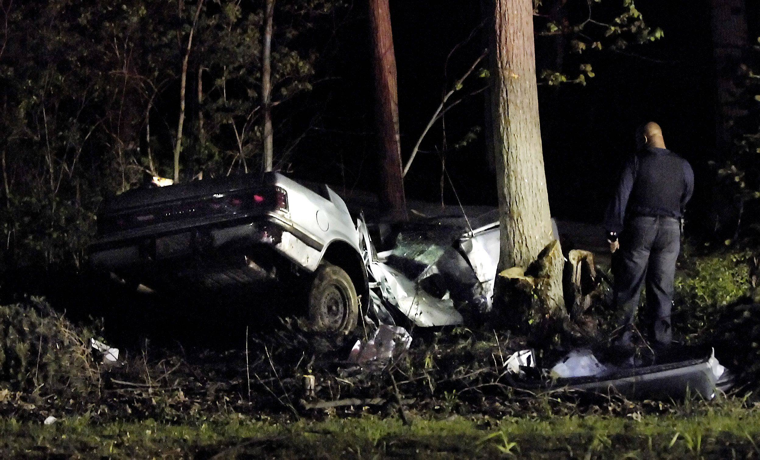 A rescuer uses a flashlight to look at the Dodge Dynasty that crashed into trees on Green Road south of Hughes Road in Elburn Monday.