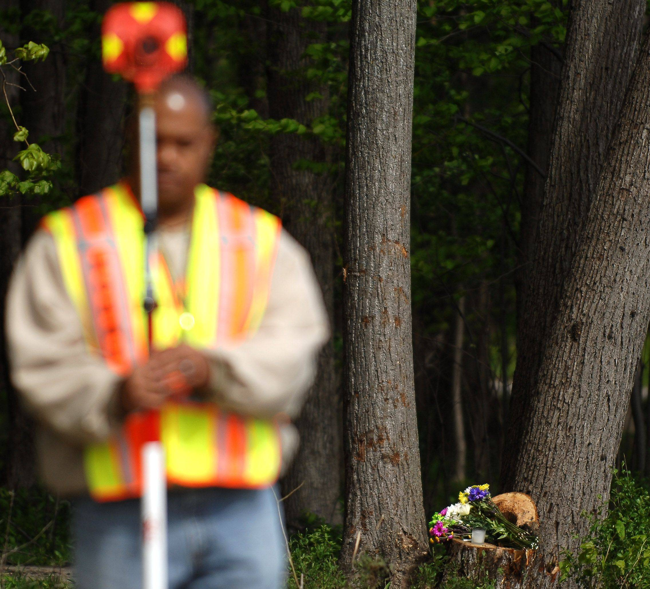 Flowers mark the site of a fatal accident on Green Road in Elburn as Kane County Sheriff's Department Sergeant Craig Campbell works to reconstruct the scene Tuesday. Batavia High School senior Lynlee Gilbert, 17, was killed in the Monday night crash and passenger Sarah Ginter, 18, is in critical condition at Delnor Hospital.