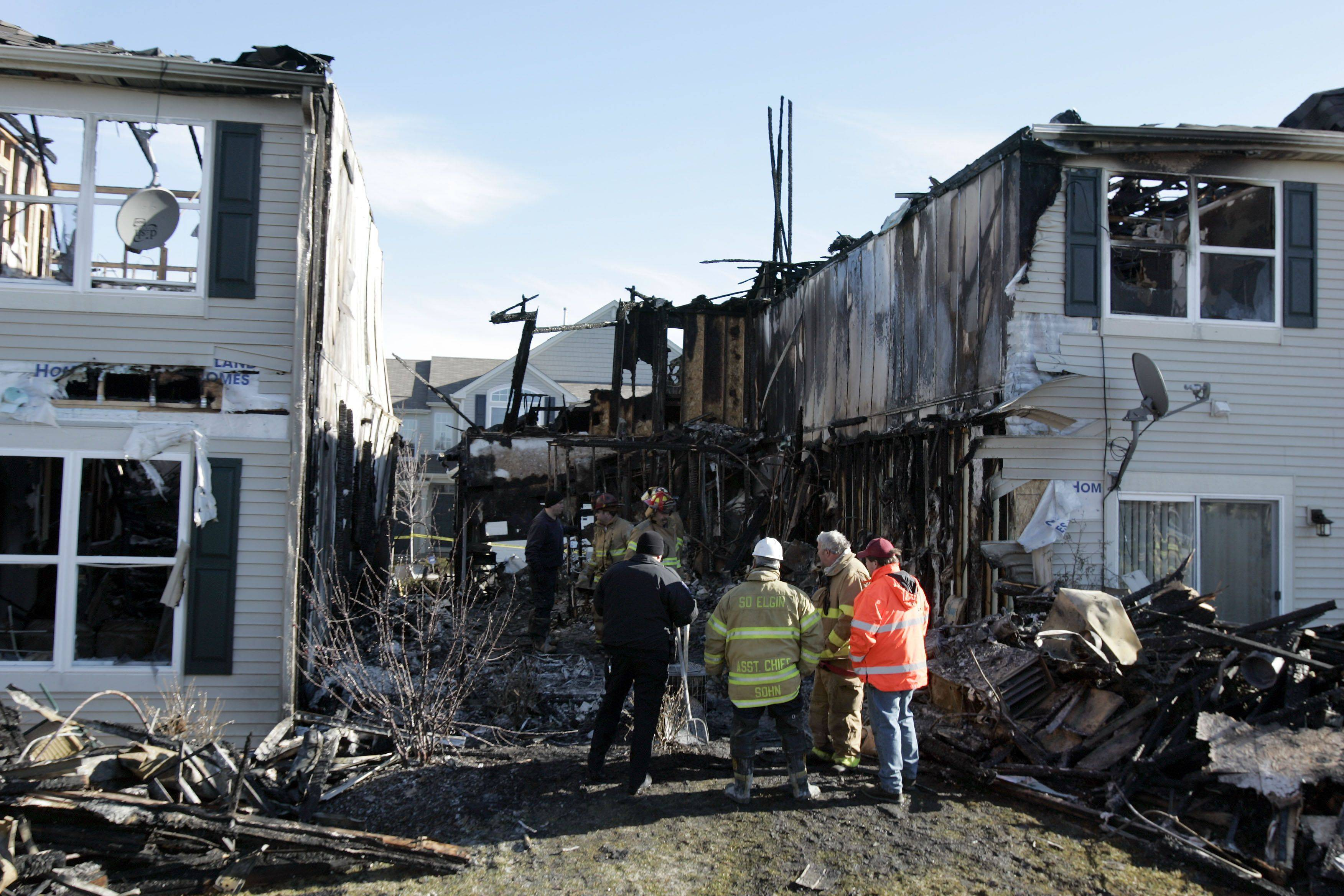 Fire personnel look over what's left of the townhouse building in the 500 block of Telluride in Gilberts four years ago. In addition to killing his girlfriend, prosecutors say, Frank Hill also torched her home.