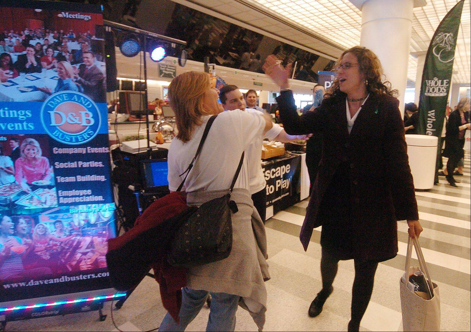 Lisa Siejko of Hoffman Estates, left, and Jenny Randag of Darien high-five each other after singing karaoke Wednesday at the Dave and Buster's booth at Chefs' Fest at Arlington Park.