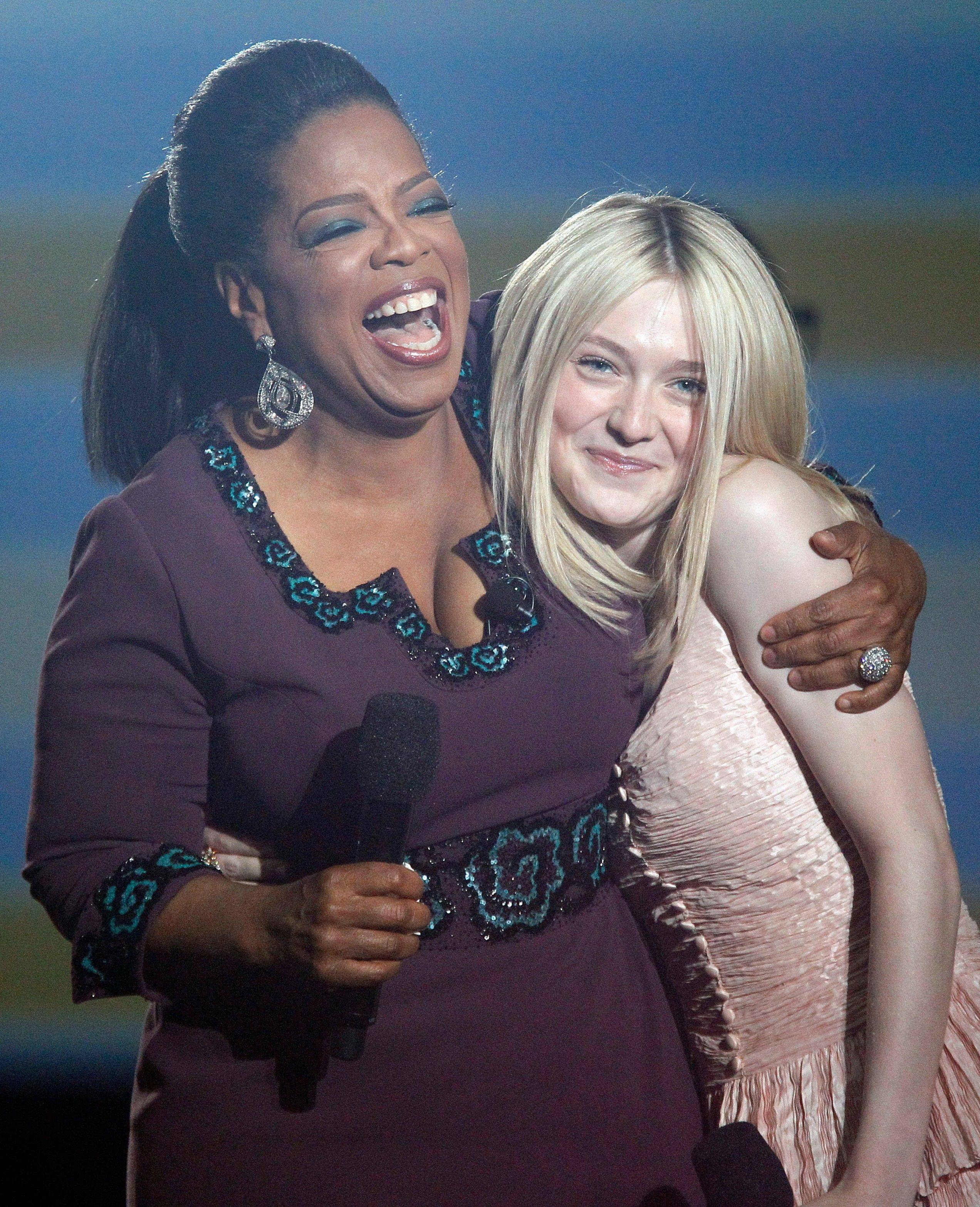 Oprah Winfrey hugs Dakota Fanning Tuesday.
