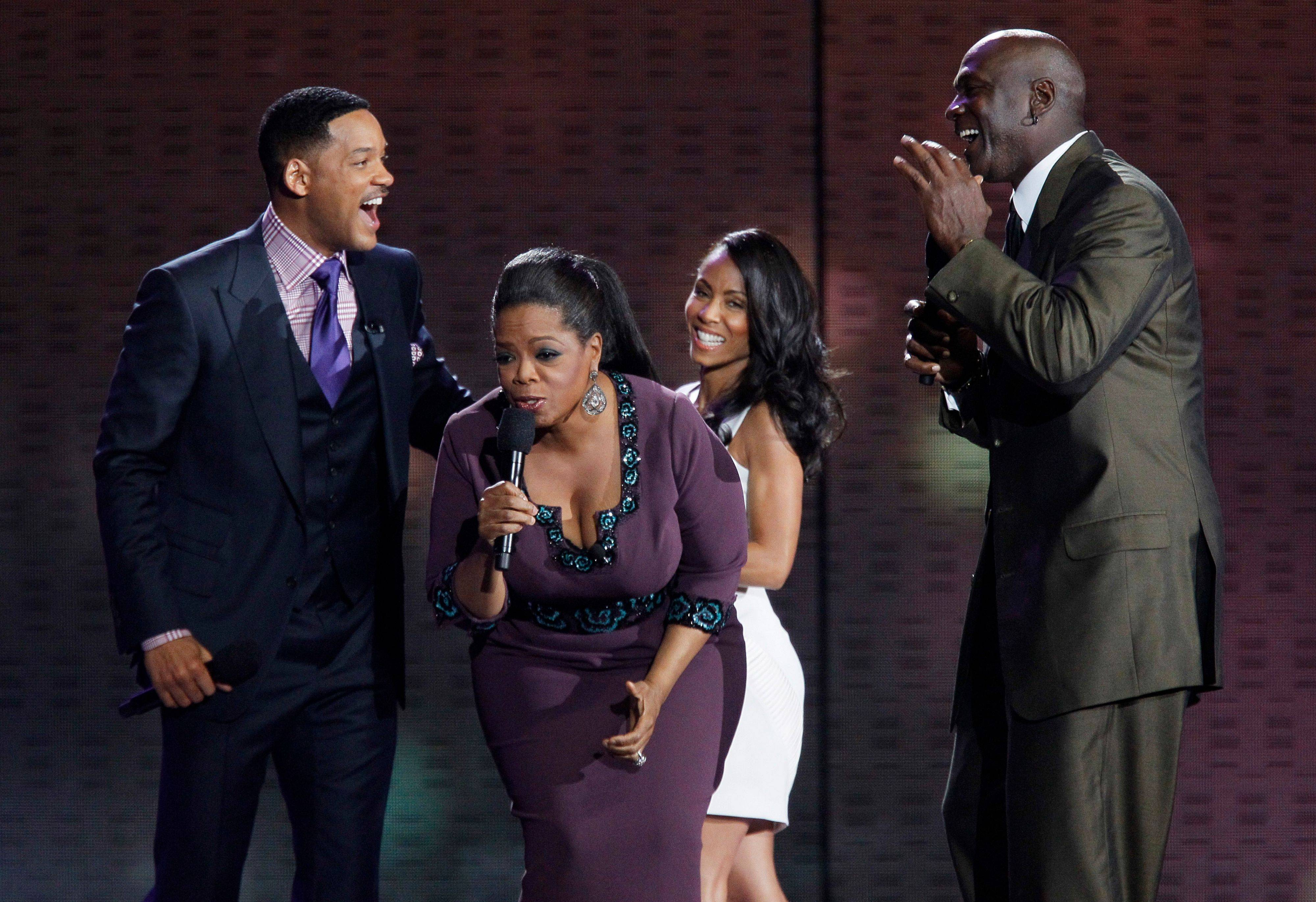 Oprah Winfrey reacts as she is surrounded by Will Smith, his wife Jada Pinkett Smith and Michael Jordan, right, on stage during the final taping Tuesday.