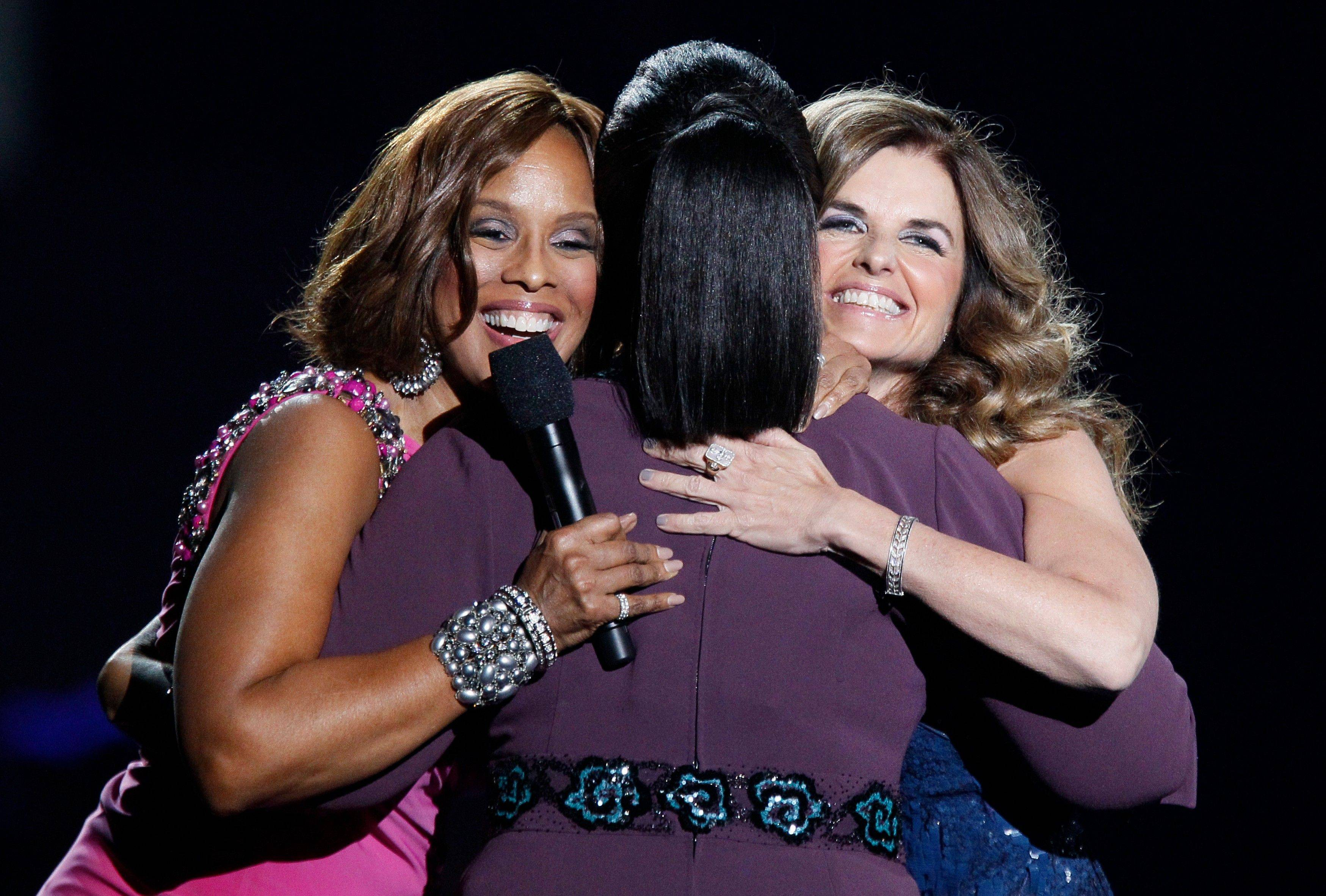 Gayle King, left, and Maria Shriver hug Oprah Tuesday.