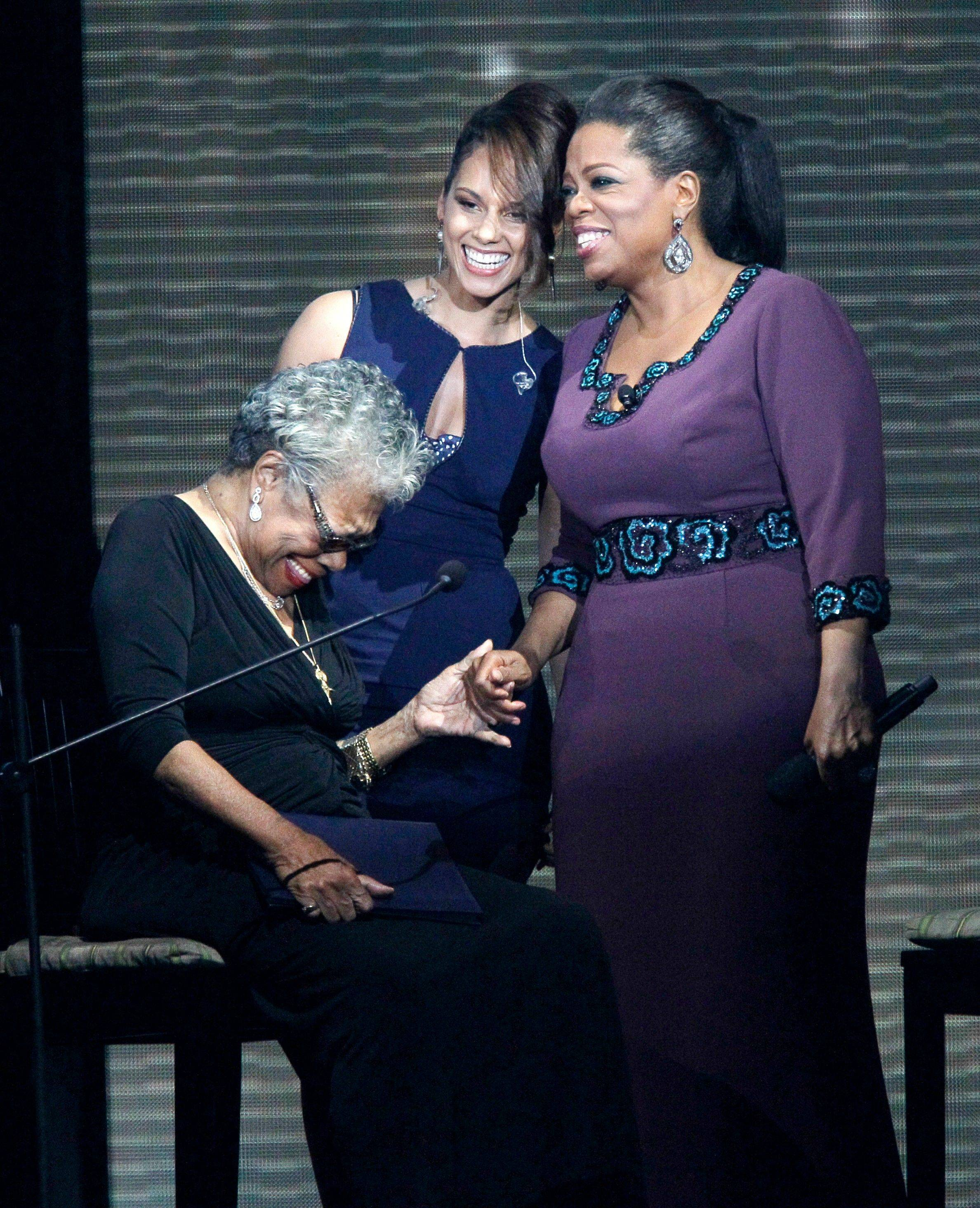 Maya Angelou, left, Alicia Keys and Oprah Winfrey laugh on stage.