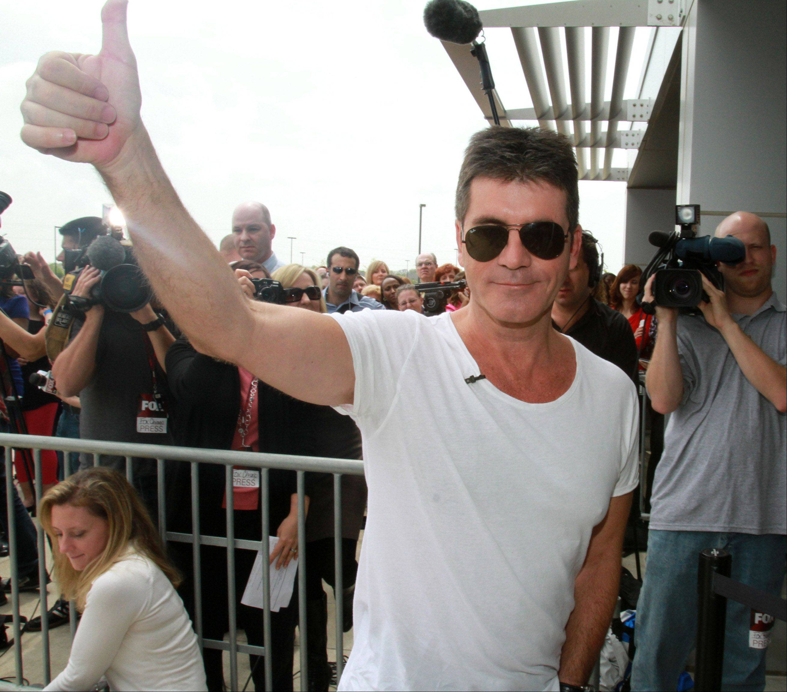 Simon Cowell give the thumbs-up as he arrives at the Sears Centre for taping of the judges round for The X Factor in Hoffman Estates on Thursday, May 19th.