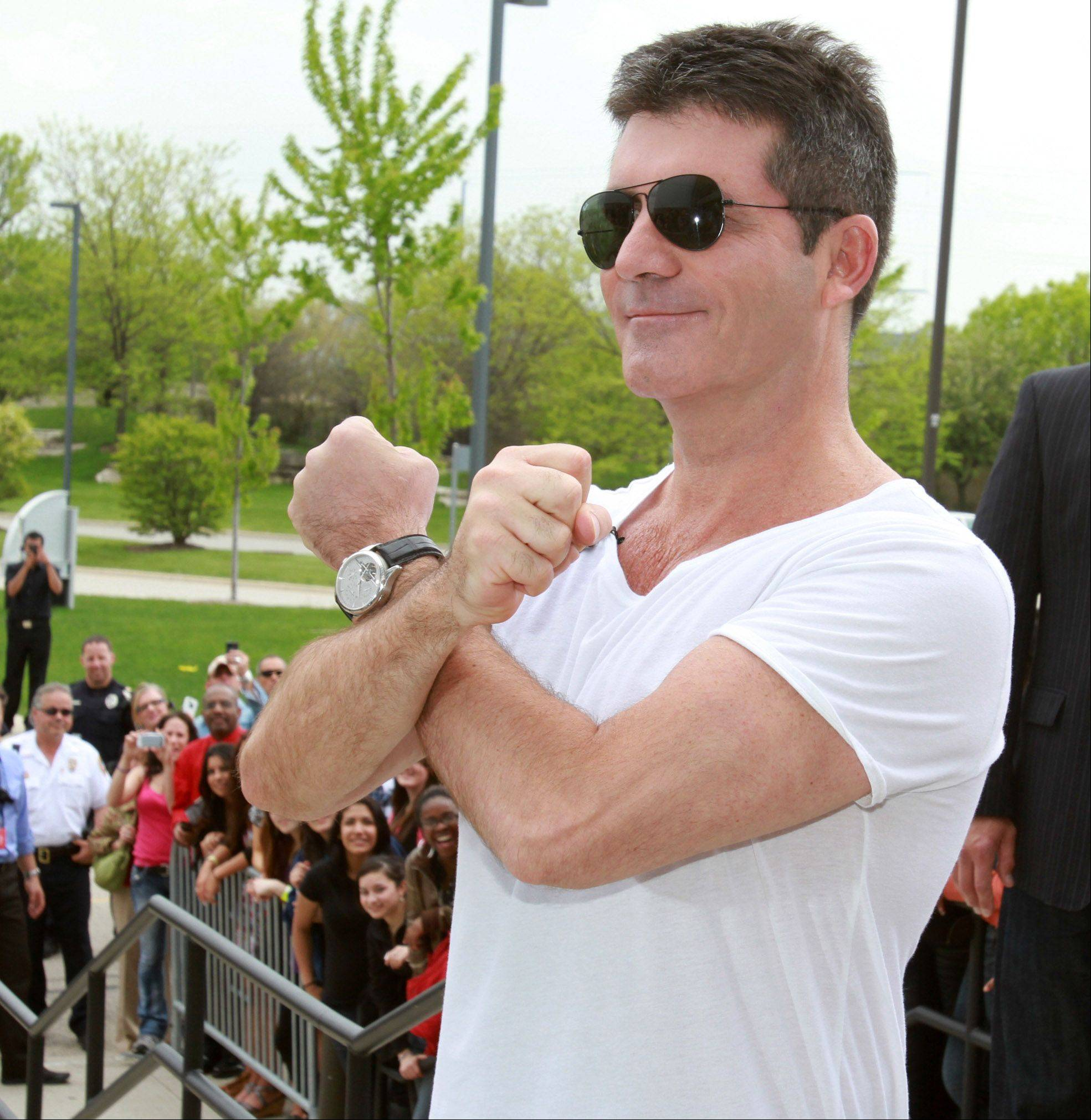 Simon Cowell makes an X sign with his arms as he arrives at the Sears Centre for taping of the judges round for The X Factor in Hoffman Estates on Thursday, May 19th.