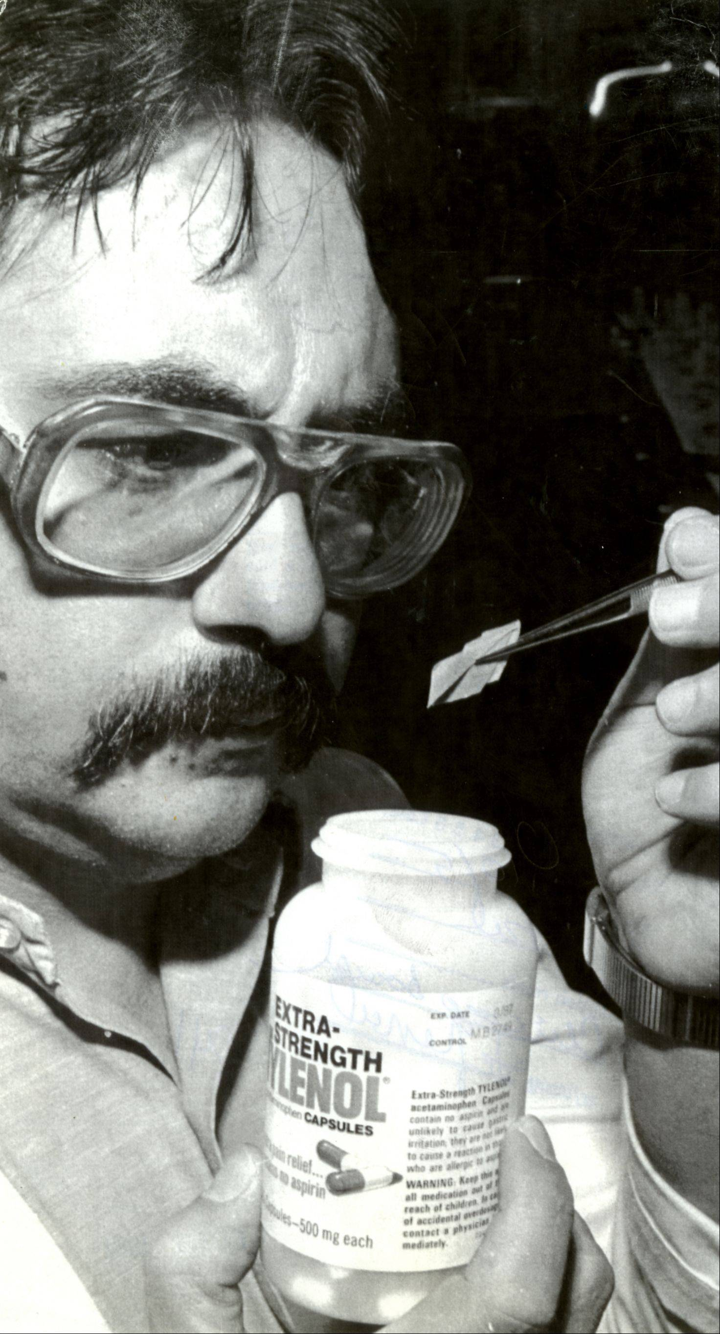 Chicago Board of Health chemist John Rasho tests Tylenol with a paper strip treated to detect cyanide.