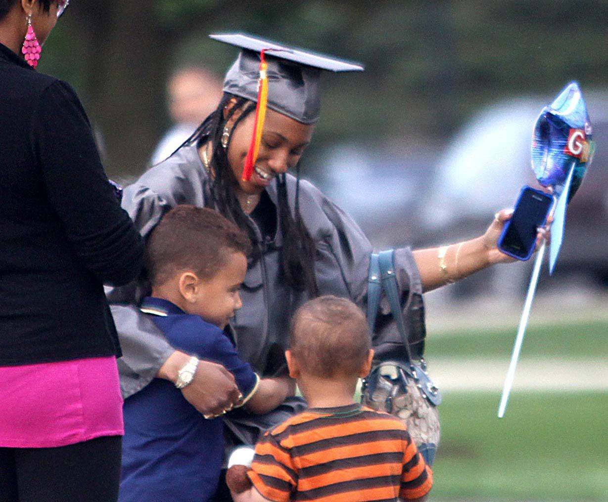 Erika Drane of Aurora greets her nephews, also from Aurora, Shane Gibson, 5, and Sylas Gibson, 2, just before commencement. Drane received an Associate in Science degree on Thursday night.