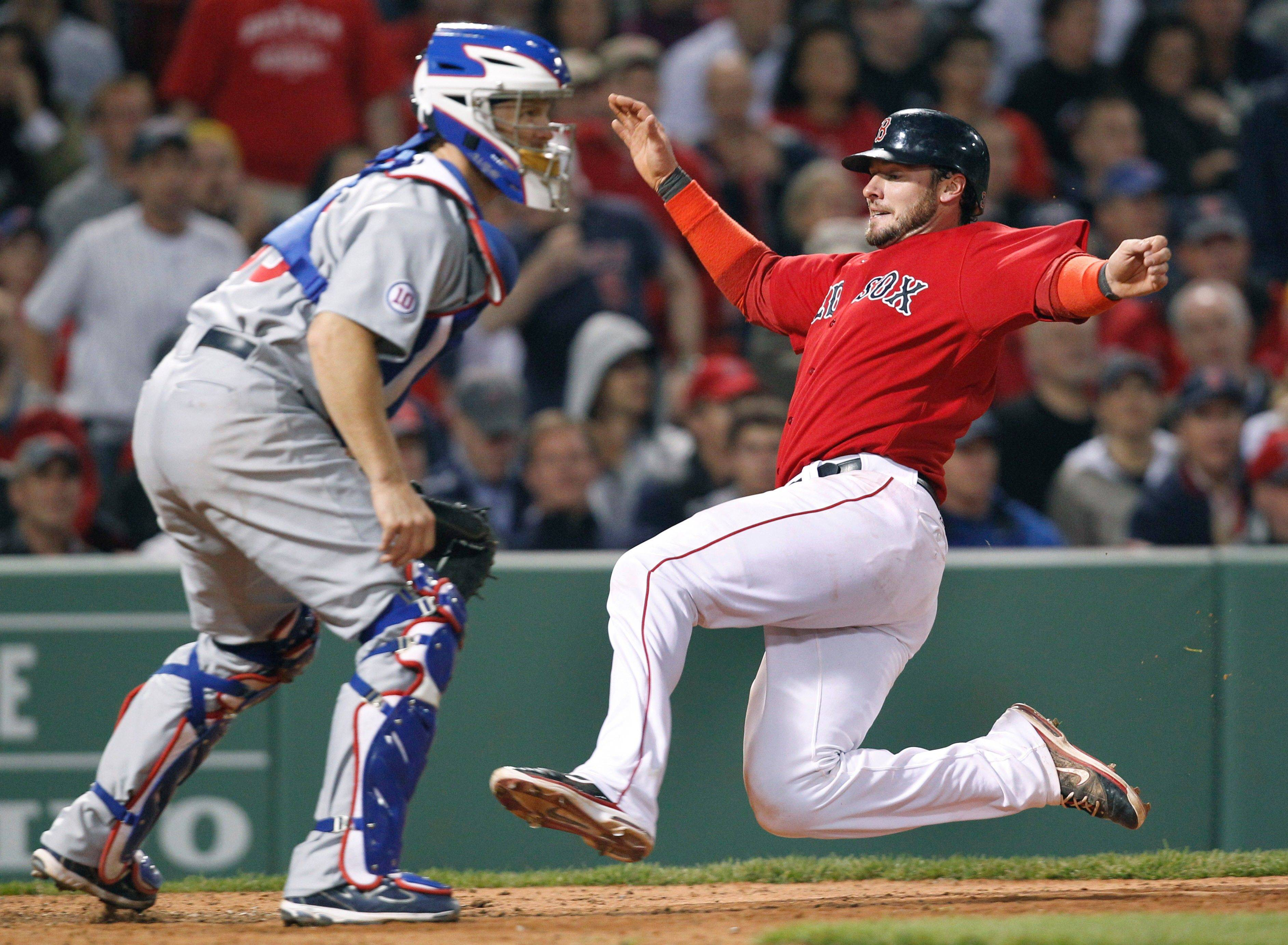 Boston Red Sox's Jarrod Saltalamacchia slides safe into home plate as Chicago Cubs catcher Koyie Hill waits for a throw on a single by Adrian Gonzalez in the eighth inning of an interleague baseball game at Fenway Park in Boston Friday, May 20, 2011. The Red Sox won 15-5.