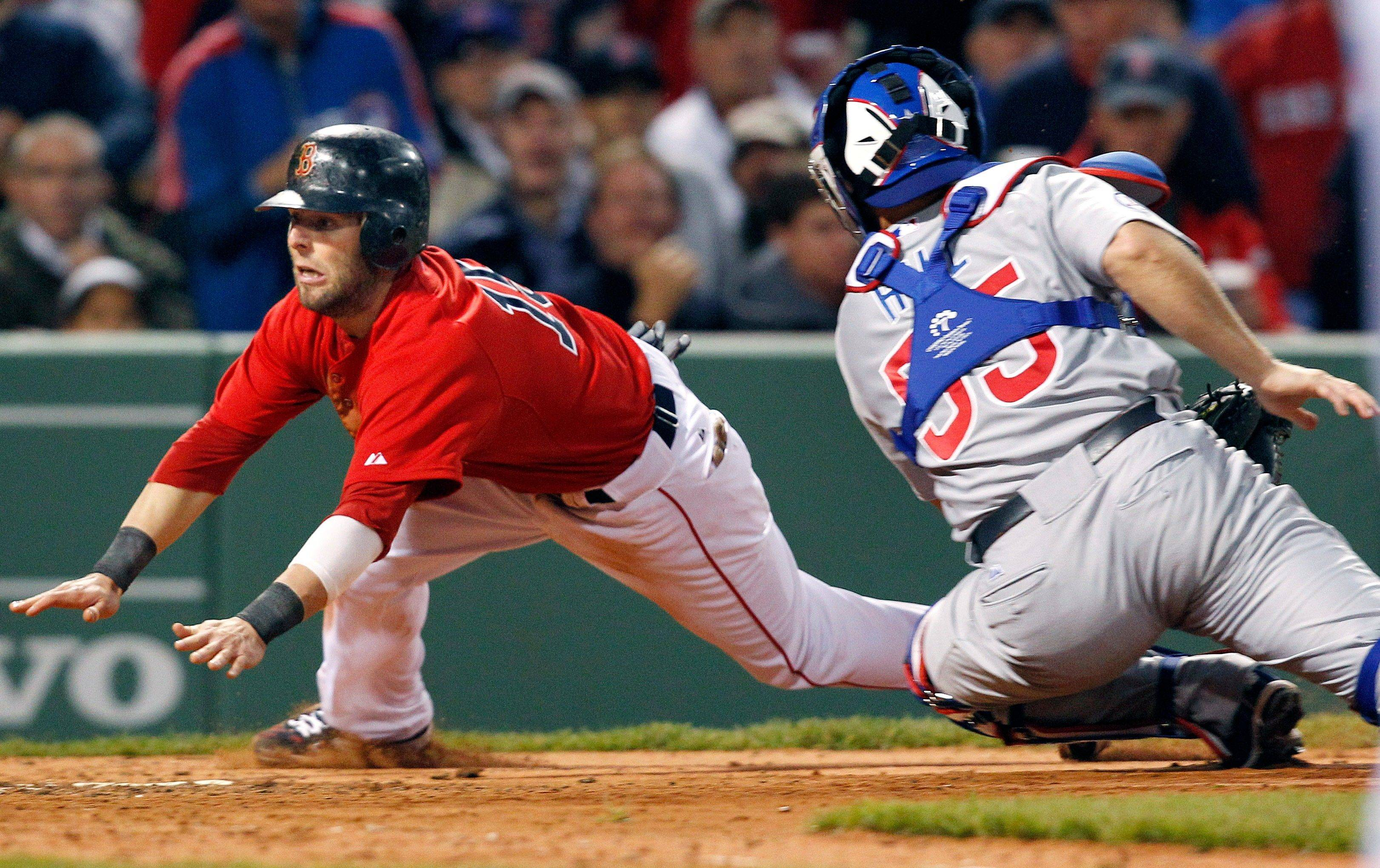 Boston Red Sox second baseman Dustin Pedroia slides safely into home on Kevin Youkilis' sacrifice fly as Chicago Cubs catcher Koyie Hill (55) cannot make the tag in the third inning of an interleague baseball game at Fenway Park in Boston Friday, May 20, 2011.