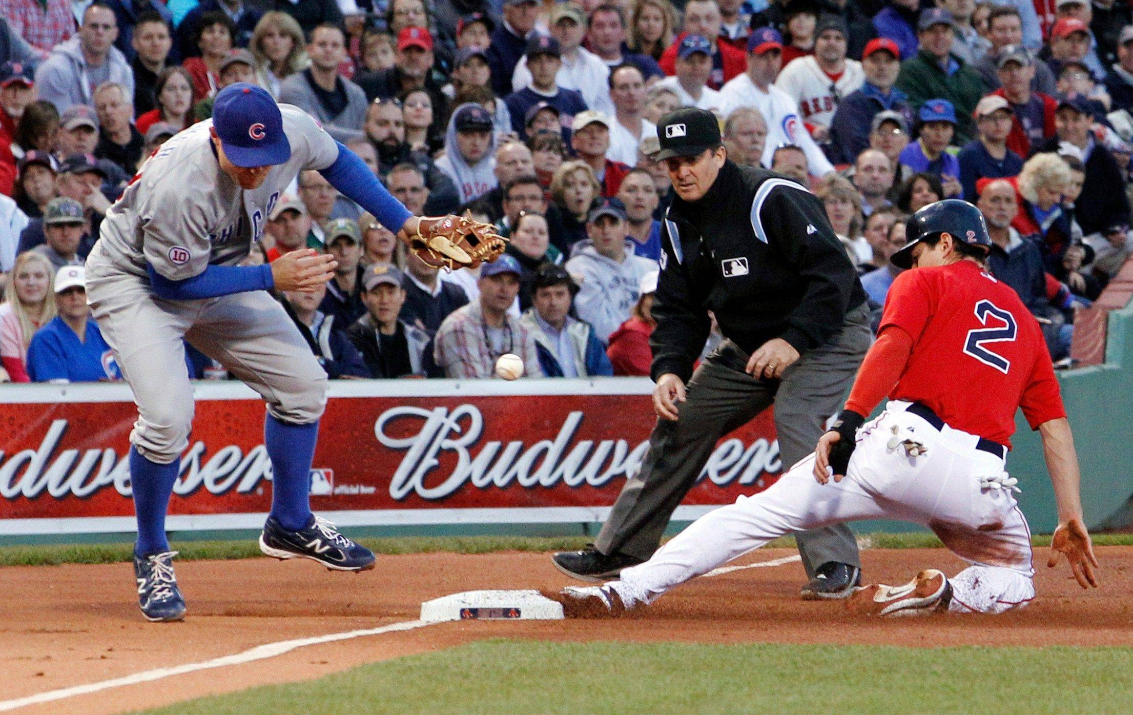 The ball gets away from Chicago Cubs third baseman Jeff Baker on a throwing error by catcher Koyie Hill as Boston Red Sox's Jacoby Ellsbury (2) steals third in the first inning of an interleague baseball game at Fenway Park in Boston Friday, May 20, 2011. Ellsbury ran home and scored on the error.