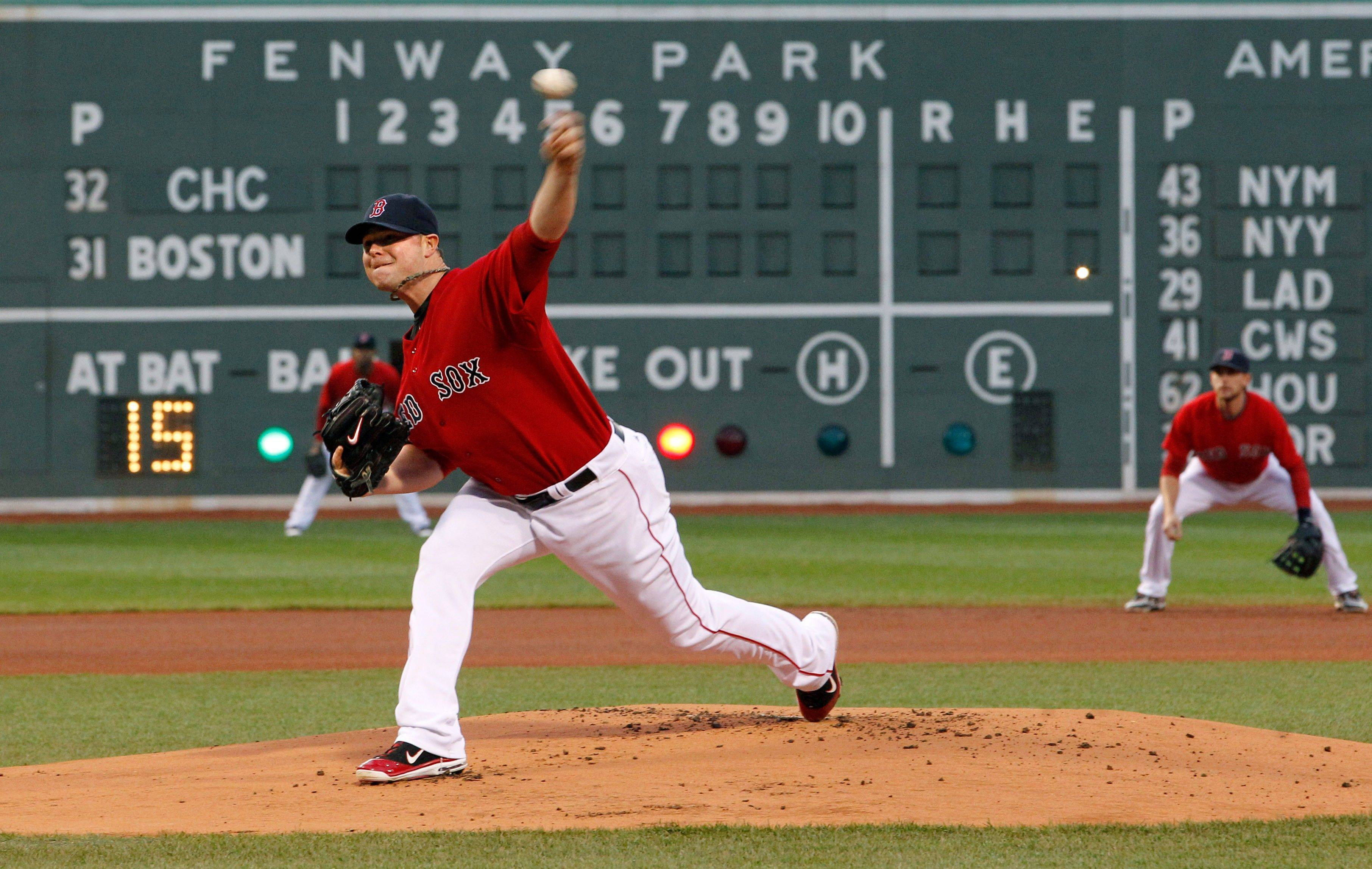 Boston Red Sox starting pitcher Jon Lester (31) delivers to the Chicago Cubs as shortstop Jed Lowrie watches in the first inning of an interleague baseball game at Fenway Park in Boston Friday, May 20, 2011.
