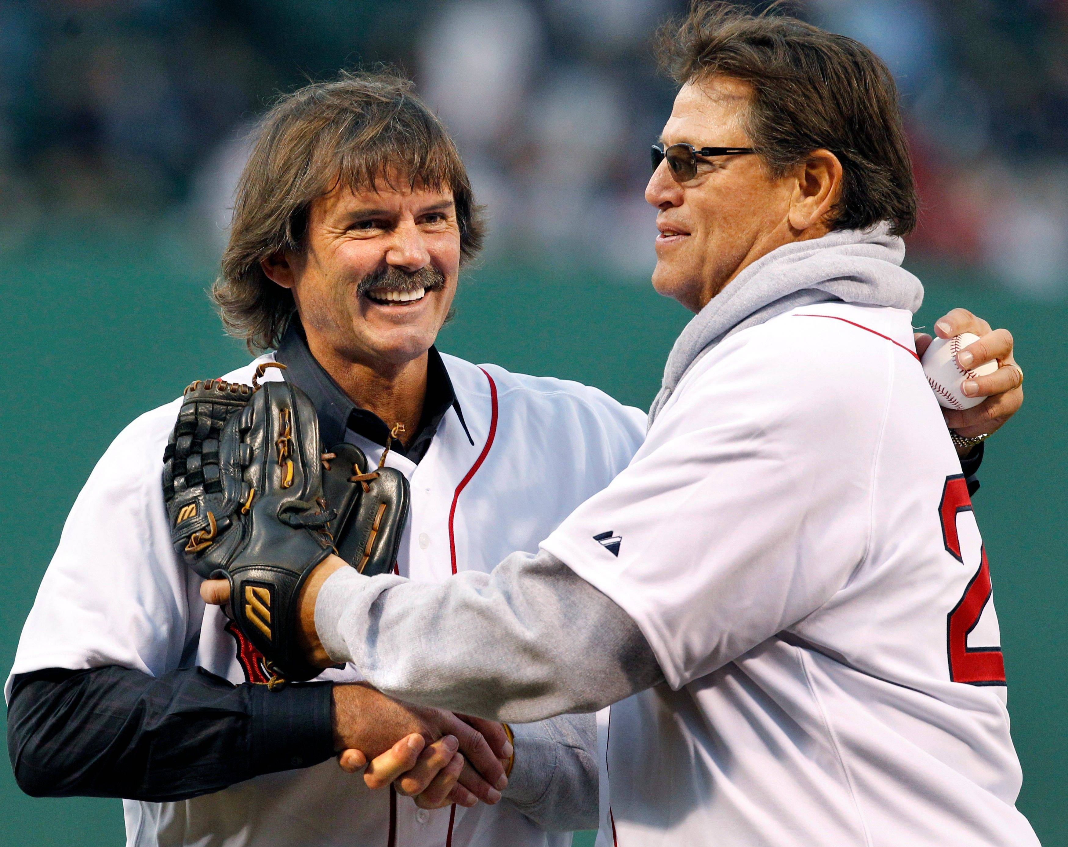 Boston Red Sox legends, pitcher Dennis Eckersley, left, and catcher Carlton Fisk shake hands after participating in the honorary first pitch prior to an interleague baseball game against the Chicago Cubs at Fenway Park in Boston Friday, May 20, 2011.
