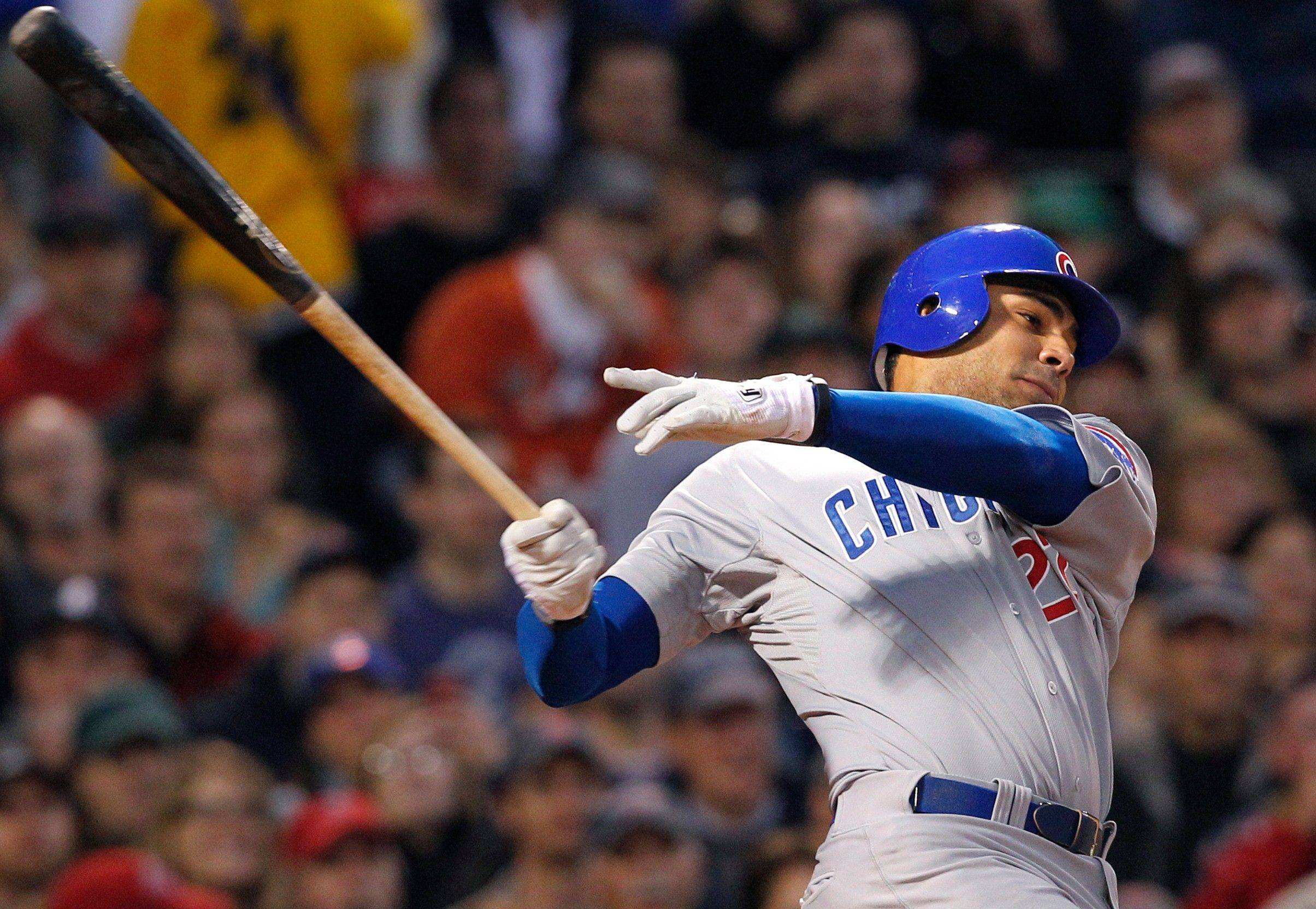 Chicago Cubs' Carlos Pena hits an RBI grounder to drive in Jeff Baker in the third inning of an interleague baseball game against the Boston Red Sox at Fenway Park in Boston Friday, May 20, 2011.