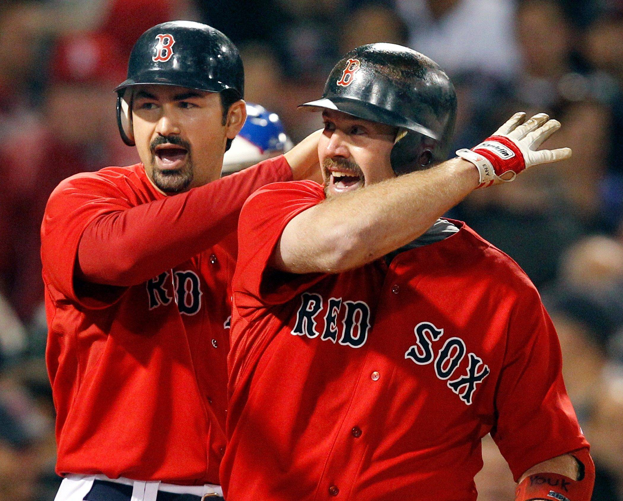 Boston Red Sox's Adrian Gonzalez, left, and Kevin Youkilis celebrate after they scored on Youkilis' two-run home run in the fourth inning of an interleague baseball game against the Chicago Cubs at Fenway Park in Boston Friday, May 20, 2011.