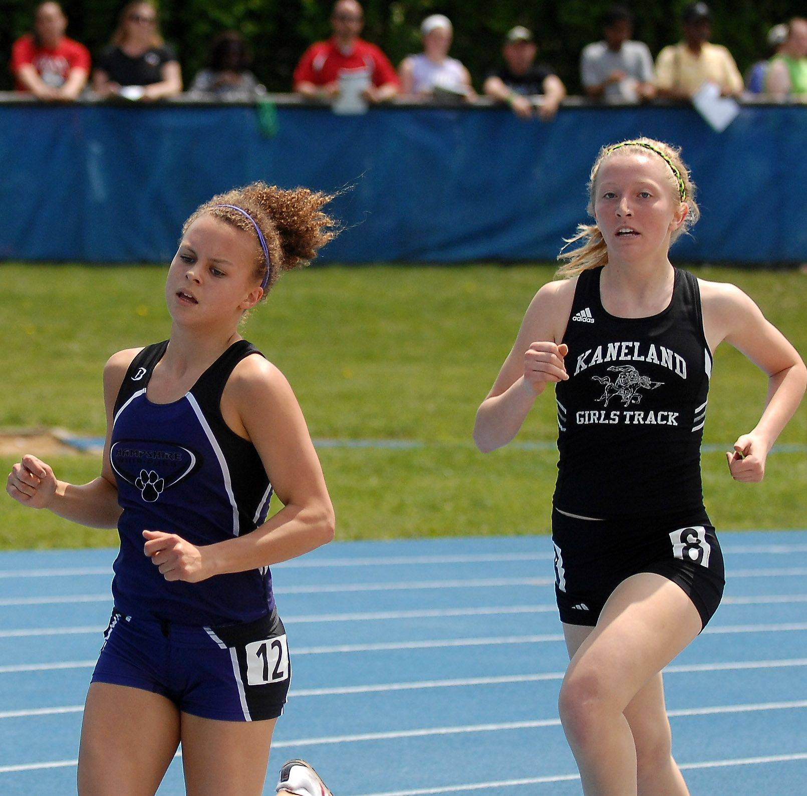 Hampshire's Cassie Kruse and Kaneland's Andie Strang run the 1600 during the preliminaries of the IHSA girls state track finals.