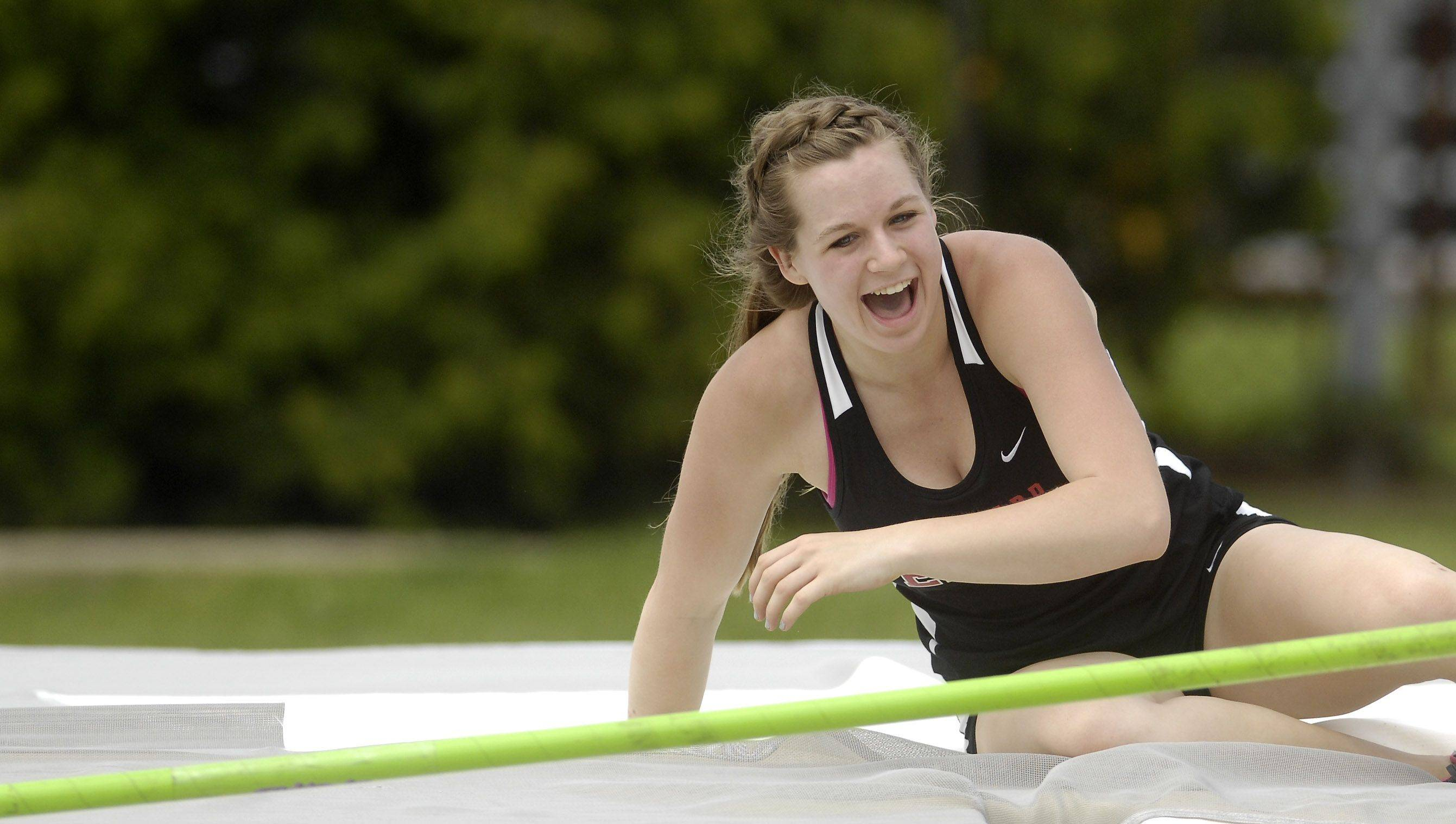 Glenbard East's Kelsey Kovach smiles after clearing the bar in the pole vault during Friday's preliminaries.