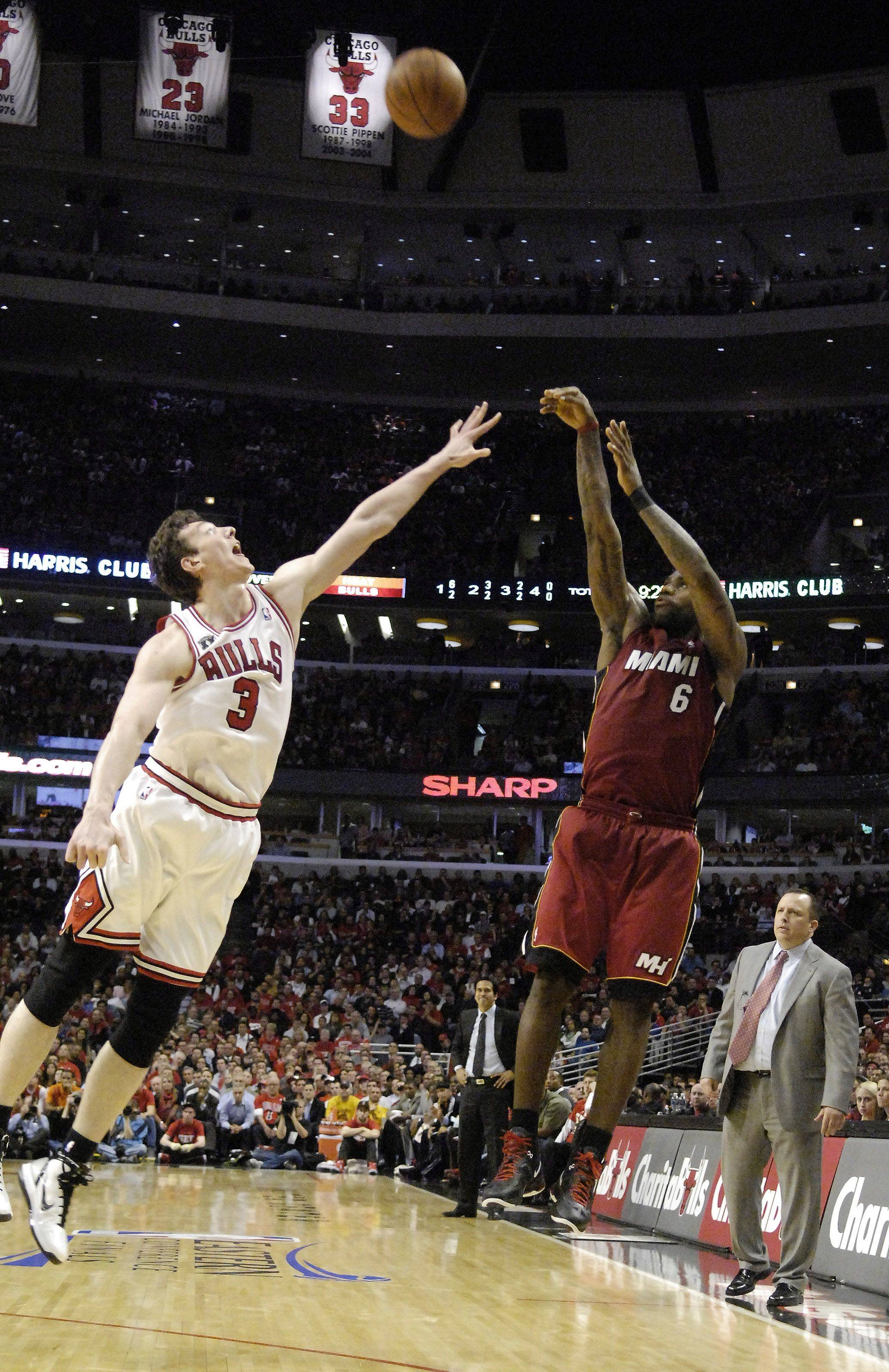 Miami Heat small forward LeBron James launches a 3-pointer over Bulls center Omer Asik during Game 2 of the NBA Eastern Conference finals at the United Center Wednesday. Game 3 is Sunday, and Asik has started every fourth quarter in this series.