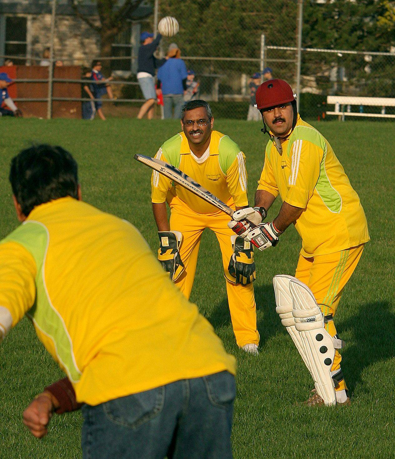 Shiran Kaushik, left, bowls to the batsman Sandeep Bhardwaj as wicket keeper Raj Kosgi observes during a demonstration last year by the Vernon Hills Cricket Club Hawks. The team plays Sunday for the first time on its home field at Century Park.
