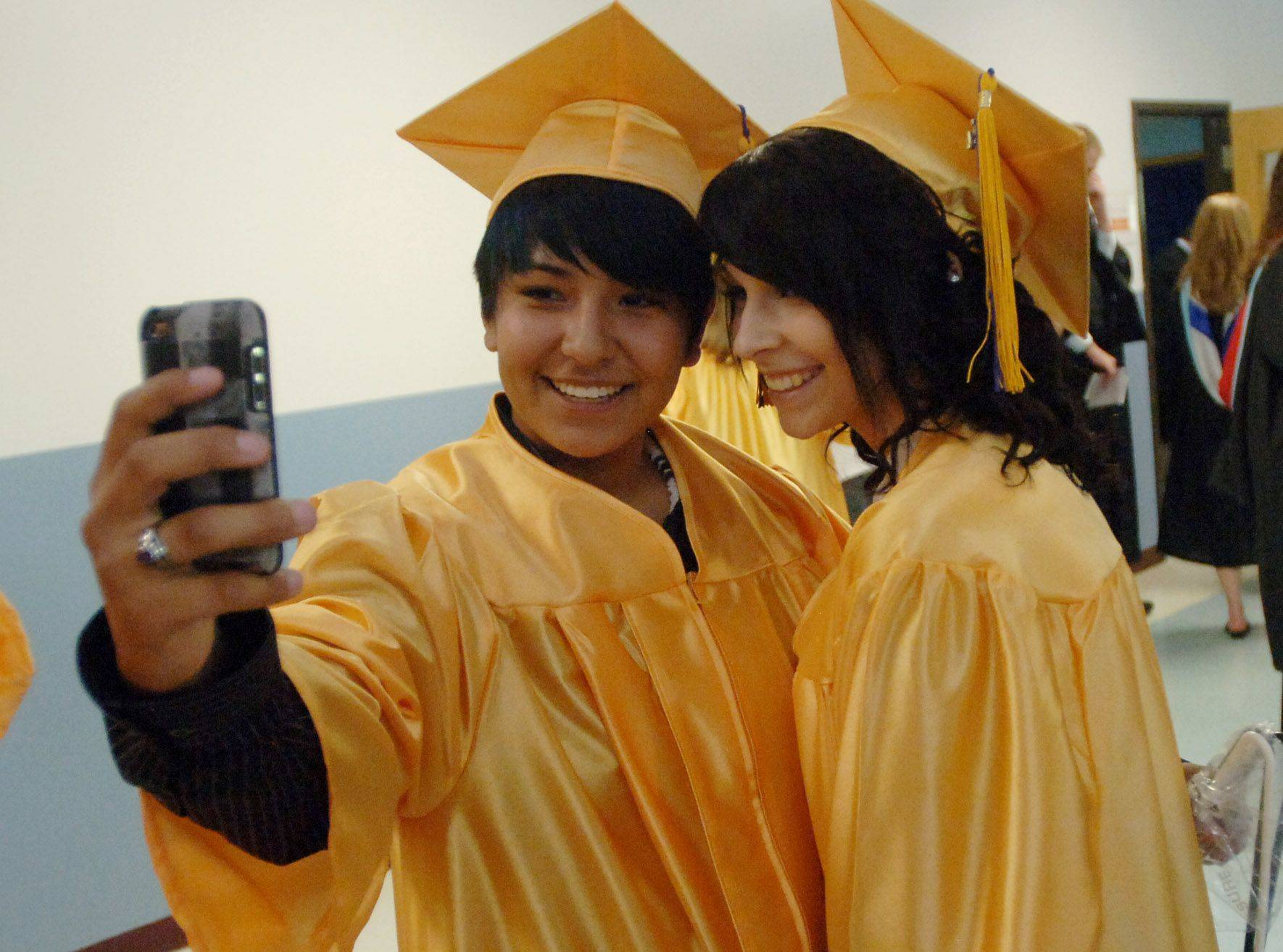 Wauconda High School graduate Alexis Lopez, left, takes photos with Ashley Brown during Sunday's commencement ceremony at the Quentin Road Bible Baptist Church in Lake Zurich.