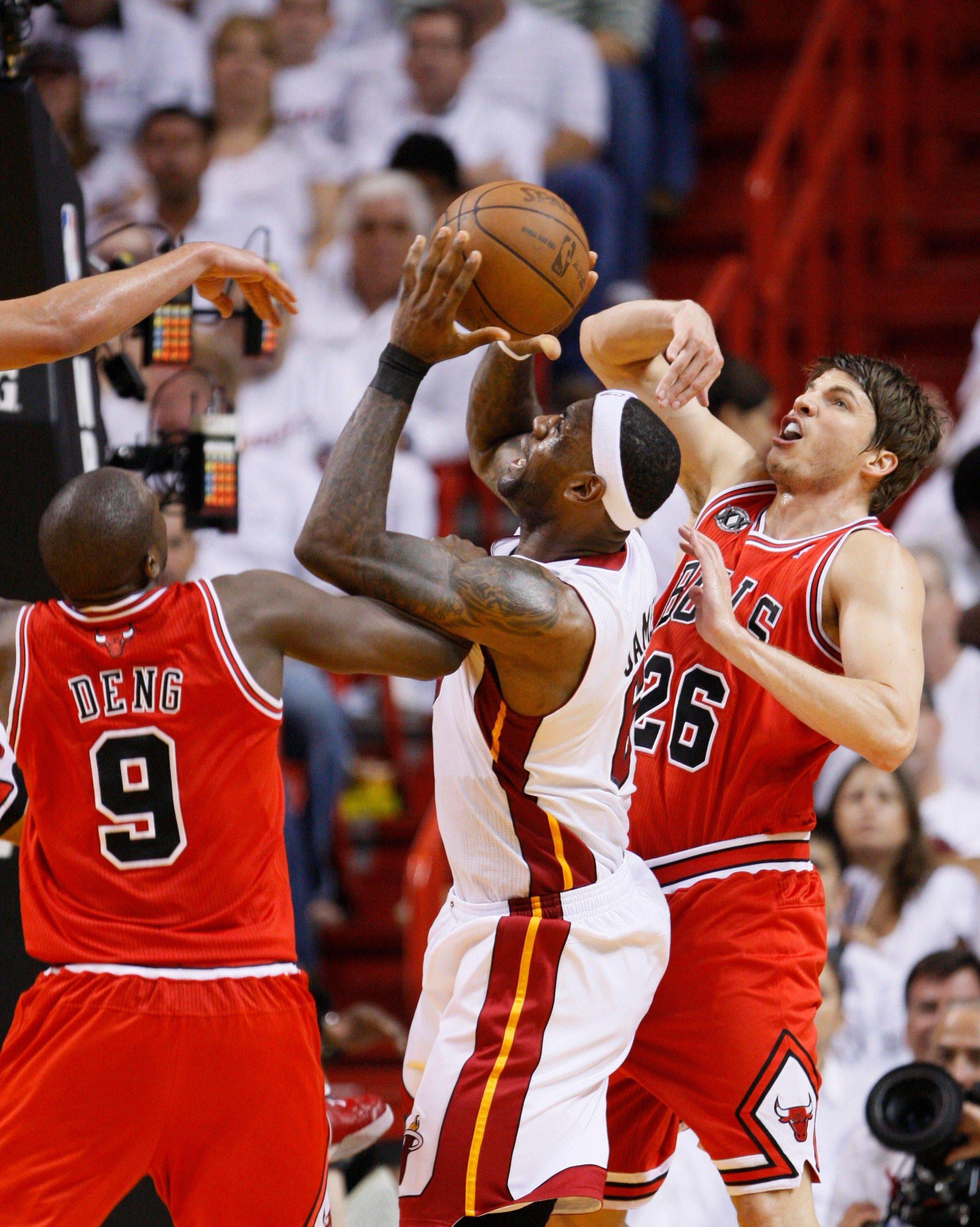Miami Heat's LeBron James, center, goes up for a shot against Chicago Bulls' Luol Deng (9) and Kyle Korver (26) during the second half of Game 3 of the NBA Eastern Conference finals basketball series in Miami, Sunday, May 22, 2011.