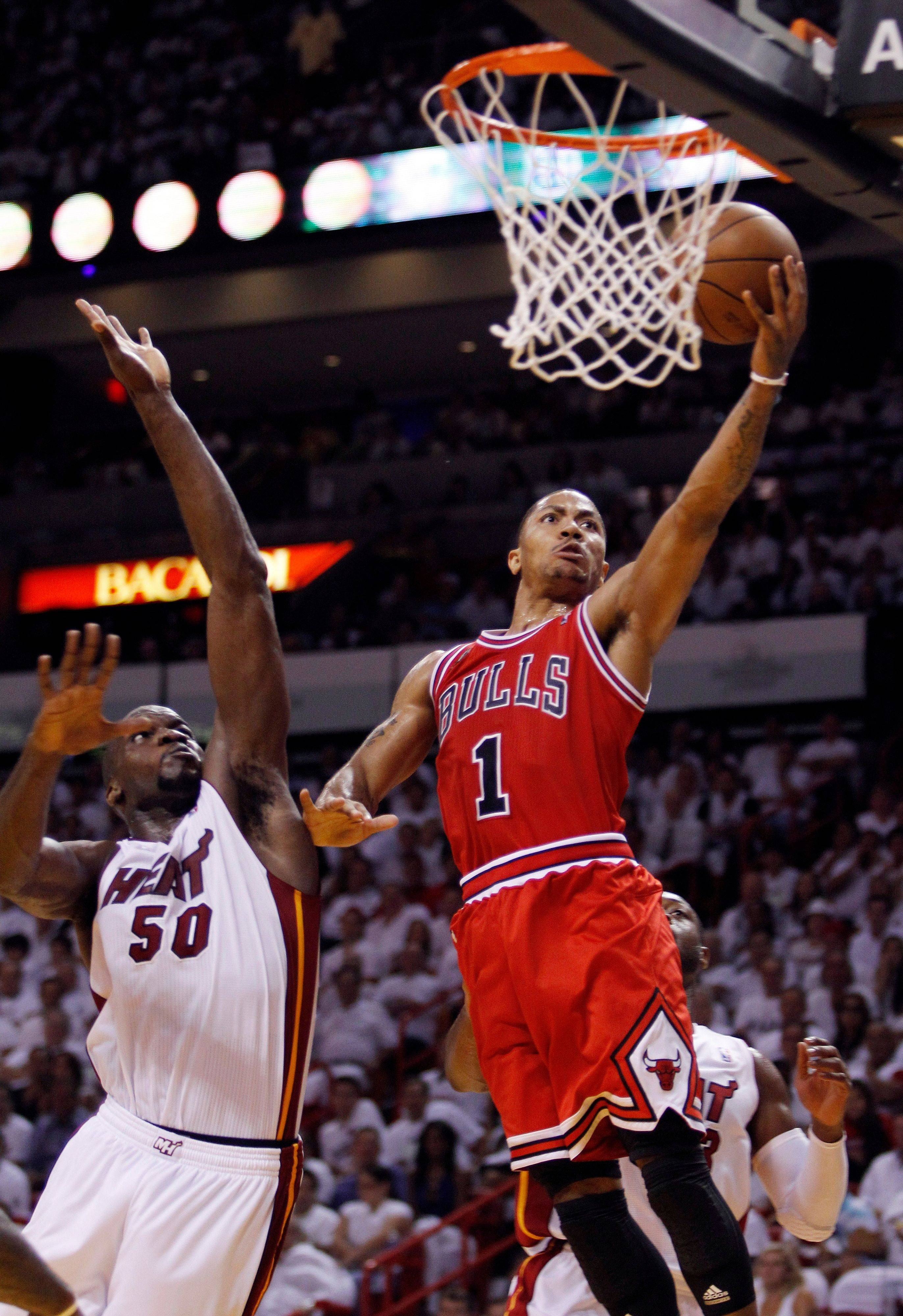 Chicago Bulls' Derrick Rose (1) goes for a basket over Miami Heat's Joel Anthony (50) and Dwyane Wade (3) during the second half of Game 3 of the NBA Eastern Conference finals basketball series in Miami, Sunday, May 22, 2011.