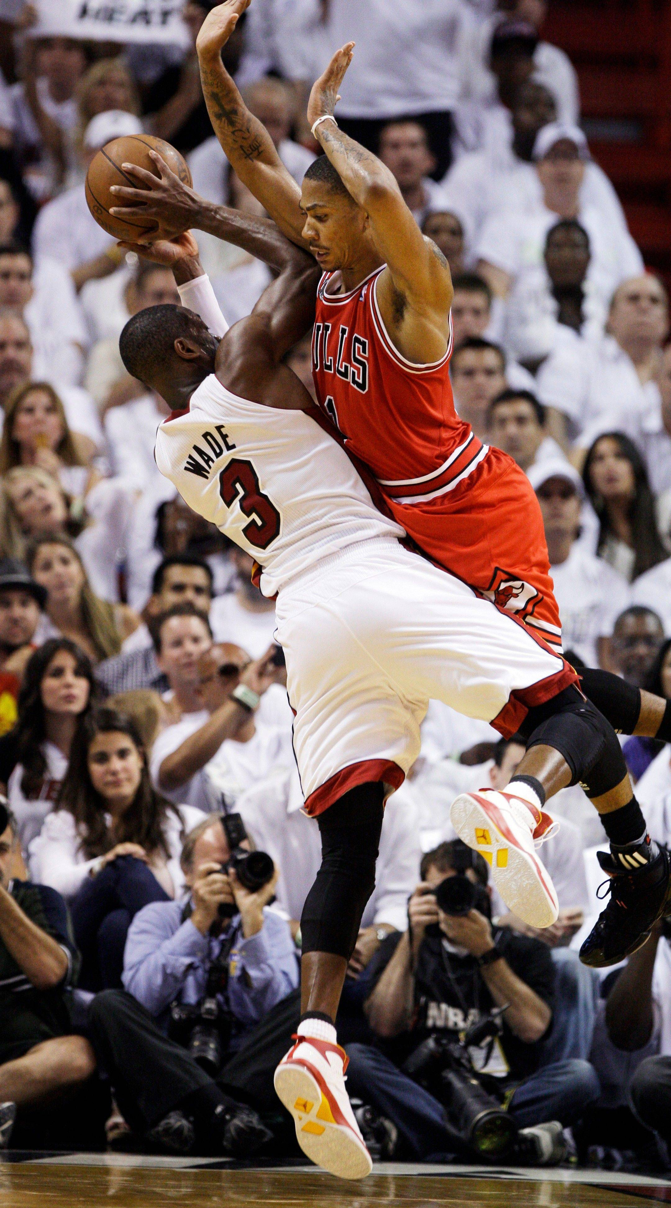 Chicago Bulls' Derrick Rose (1) collides with Miami Heat's Dwyane Wade (3) during the second half of Game 3 of the NBA Eastern Conference finals basketball series in Miami, Sunday, May 22, 2011. The Heat defeated the Bulls 96-85.