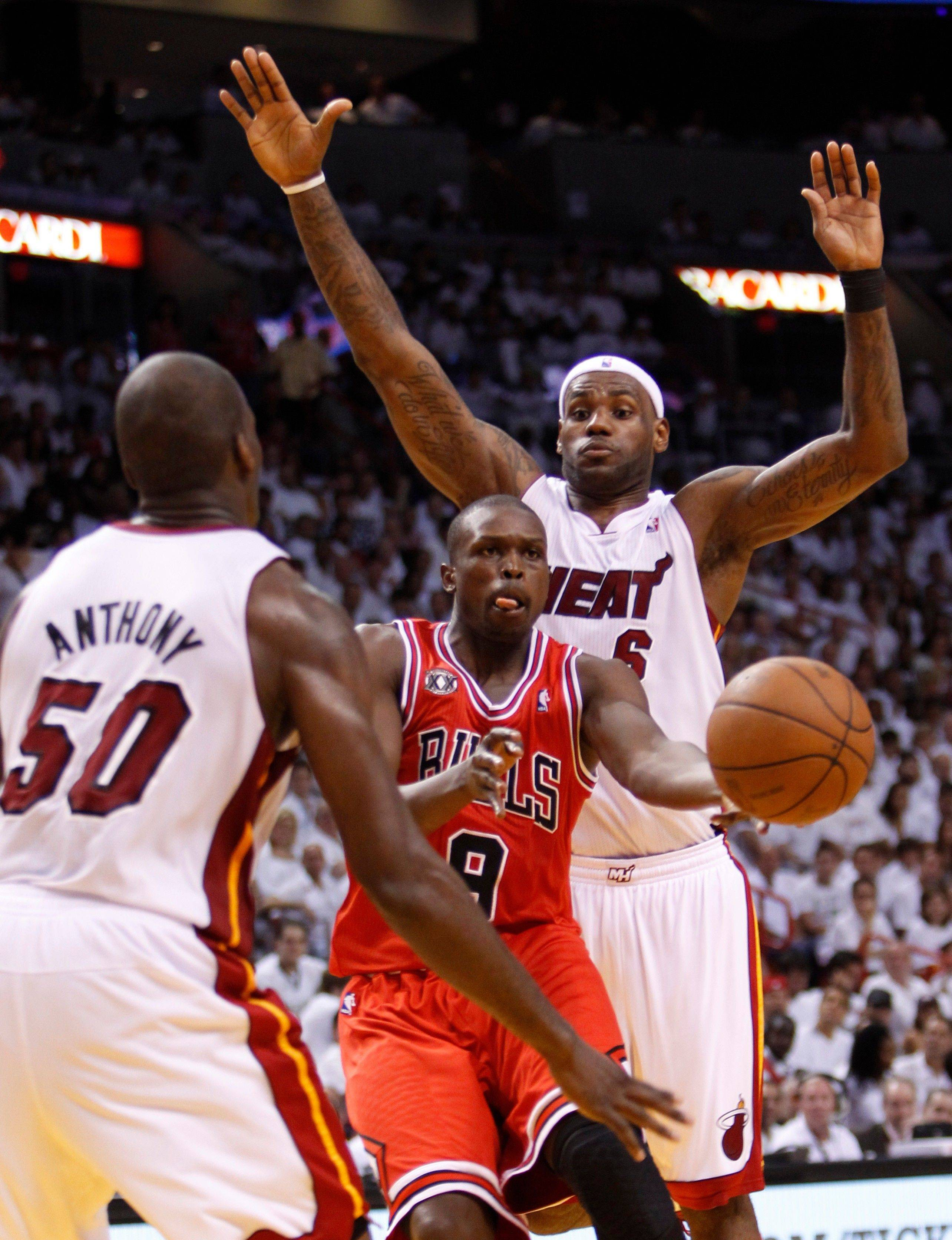 Chicago Bulls' Luol Deng, center, passes to a teammate past Miami Heat's Joel Anthony (50) and LeBron James, rear, during the second half of Game 3 of the NBA Eastern Conference finals basketball series in Miami, Sunday, May 22, 2011.