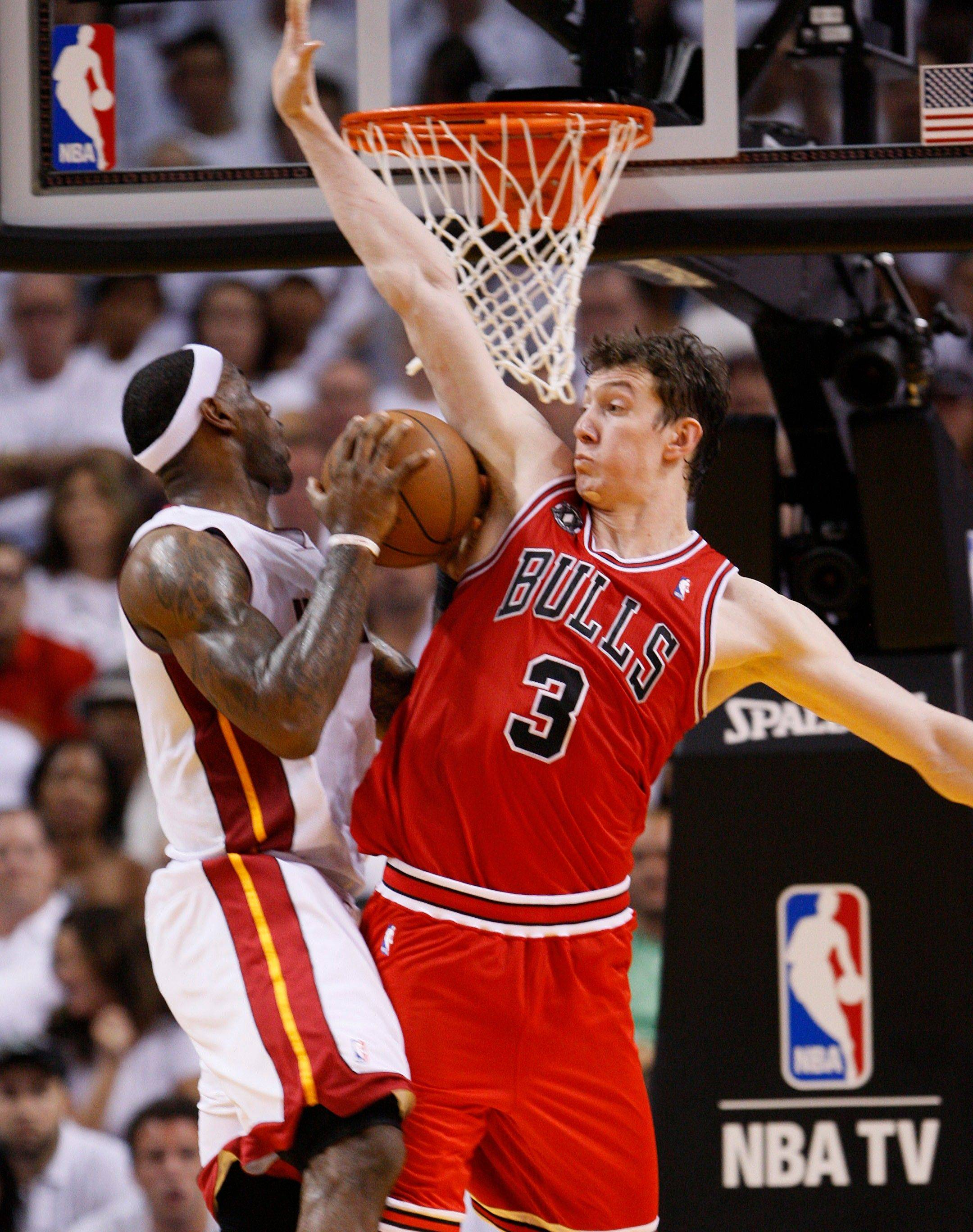 Miami Heat's LeBron James, left, goes up for a shot against Chicago Bulls' Omer Asik (3) during the second half of Game 3 of the NBA Eastern Conference finals basketball series in Miami, Sunday, May 22, 2011.