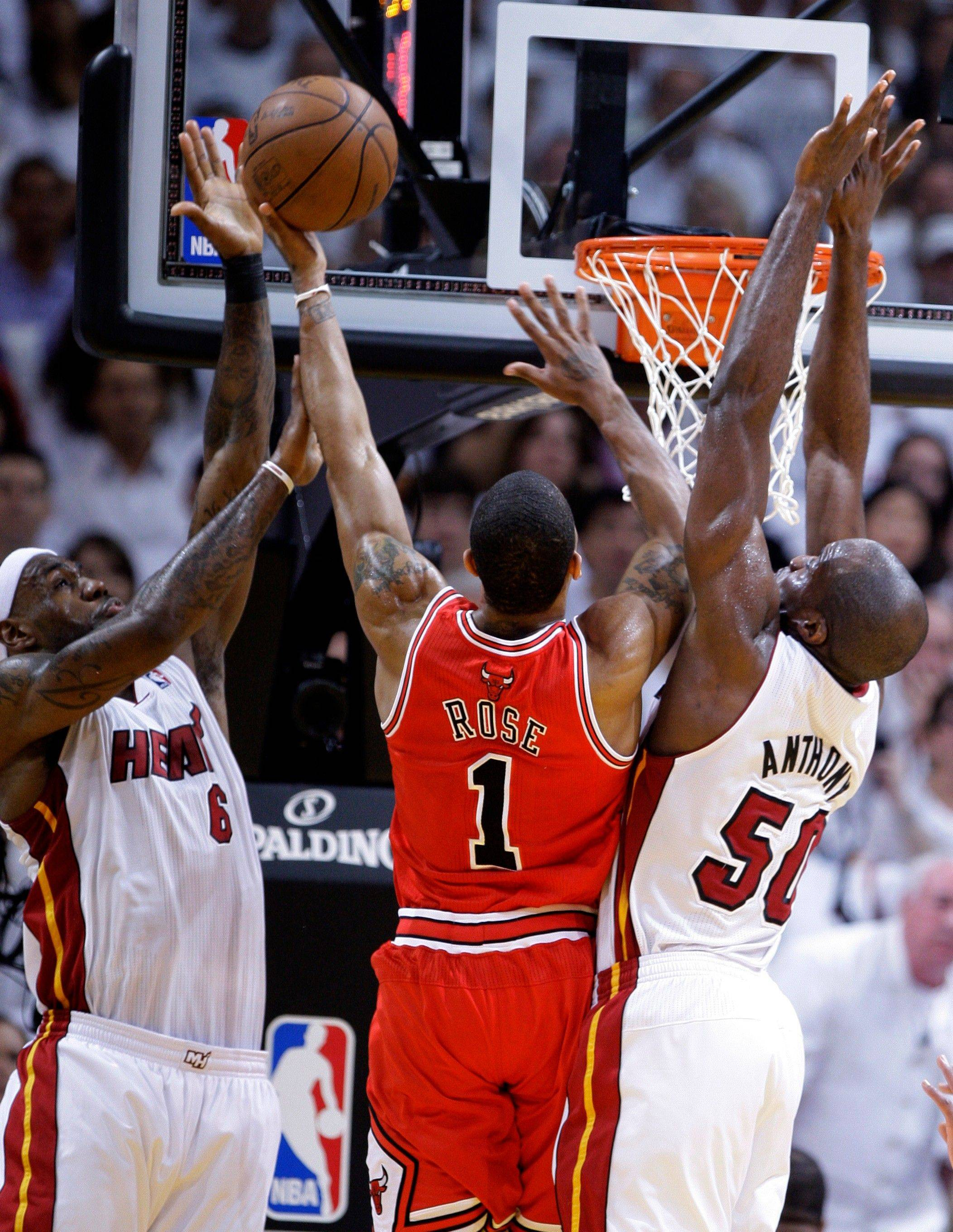 Miami Heat's LeBron James (6) and Joel Anthony (50) stop Derrick Rose's drive to the basket during the first half of Game 3 of the NBA Eastern Conference finals basketball series in Miami, Sunday, May 22, 2011.