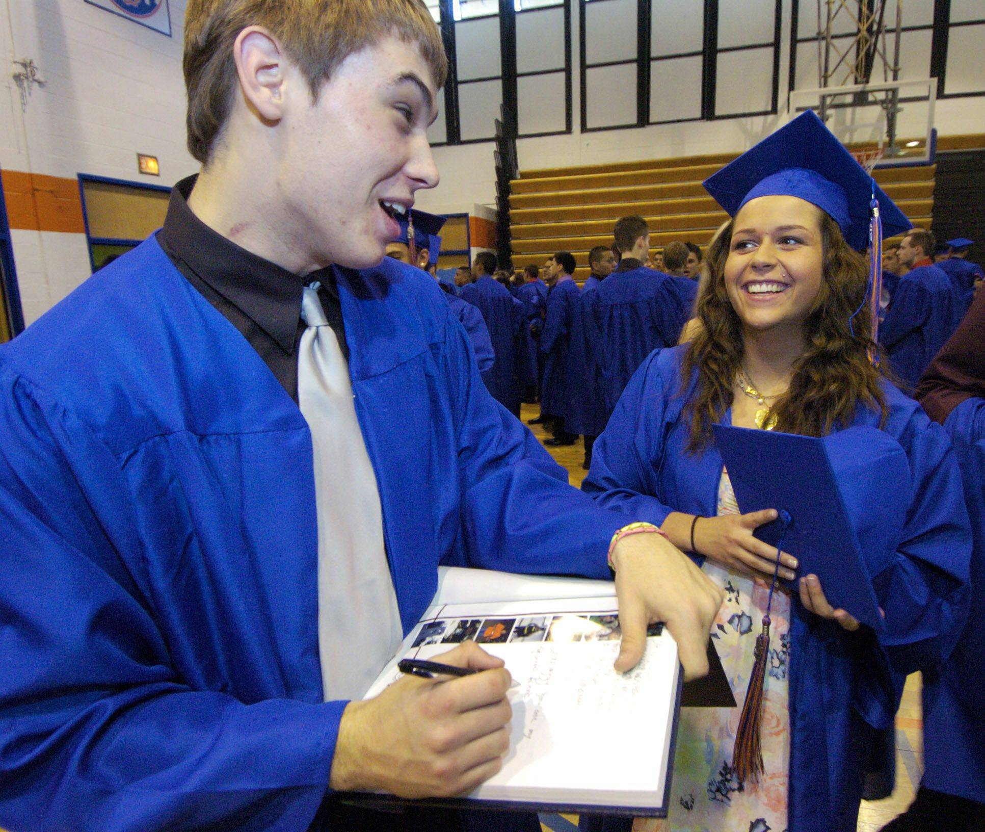 Colin Byrne chats with Liz Berley as he autographs a yearbook for another friend prior to the Fenton High School graduation Sunday.