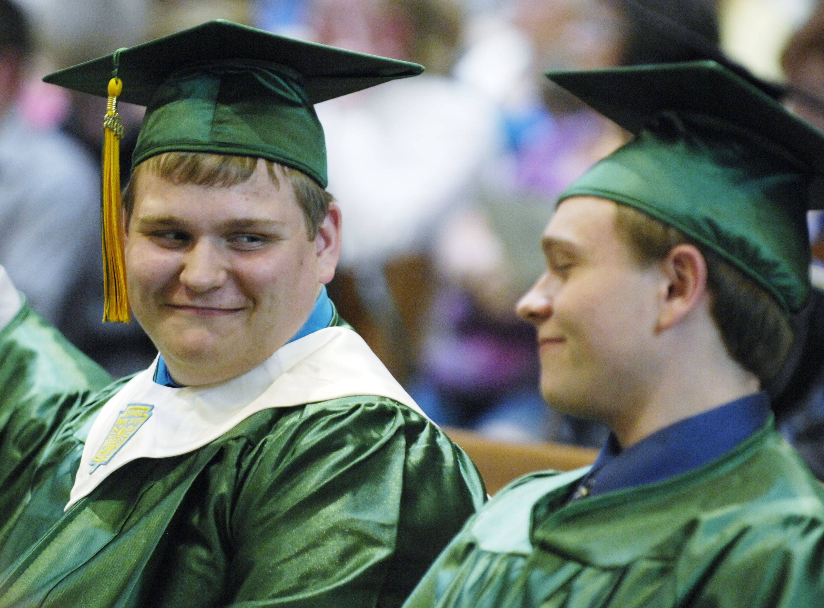 Graduates Zachary Trisilla, left, and Jeffrey Tschumper, share a moment of pride during Elgin's St. Edward Central Catholic High School Class of 2011 graduation ceremony Tuesday at St. Patrick Church in St. Charles.